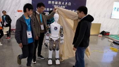 "In this Friday, Oct. 21, 2016 photo, Chinese college students remove the cover from the Ares, a humanoid bipedal robot designed by them with fundings from a Shanghai investment company, displayed during the World Robot Conference in Beijing. China is showcasing its burgeoning robot industry as it seeks to promote use of more advanced technologies in Chinese factories and create high-end products that redefine the meaning of ""Made in China."" The Ares is a human-sized robot they designed with exposed metal arms and hands and a wide range of uses in mind, from the military to performing basic tasks in a home. (AP Photo/Ng Han Guan)"