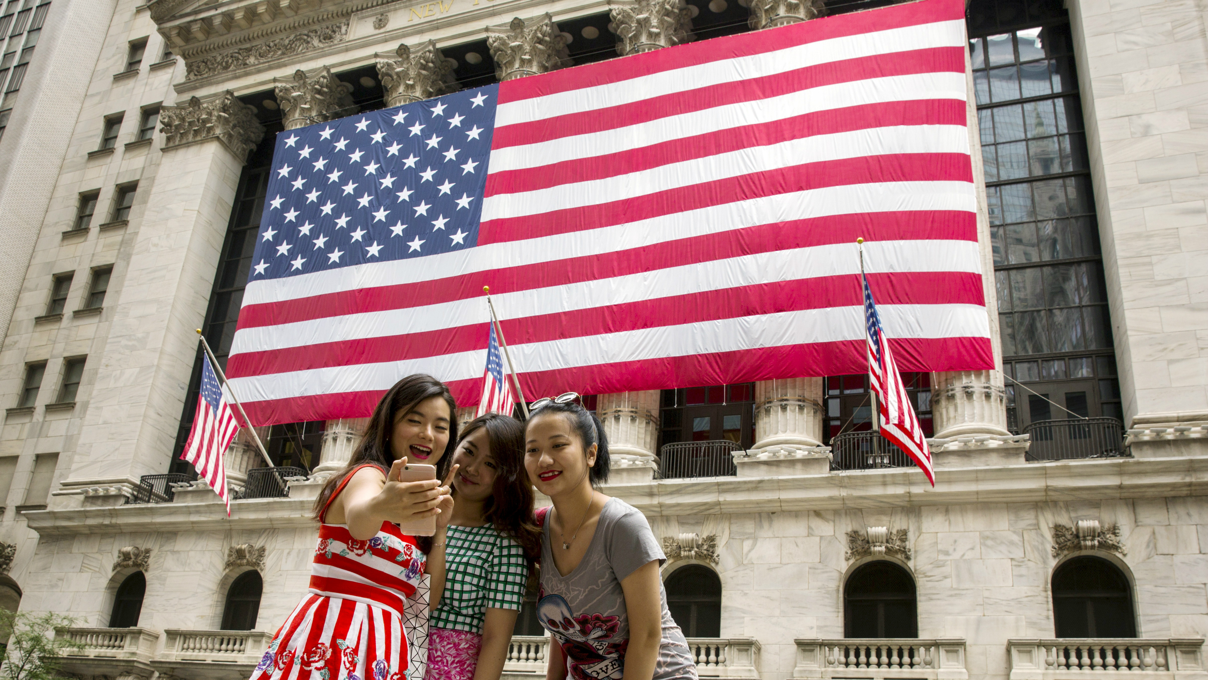 Chinese tourists take photographs of themselves outside of the New York Stock Exchange.