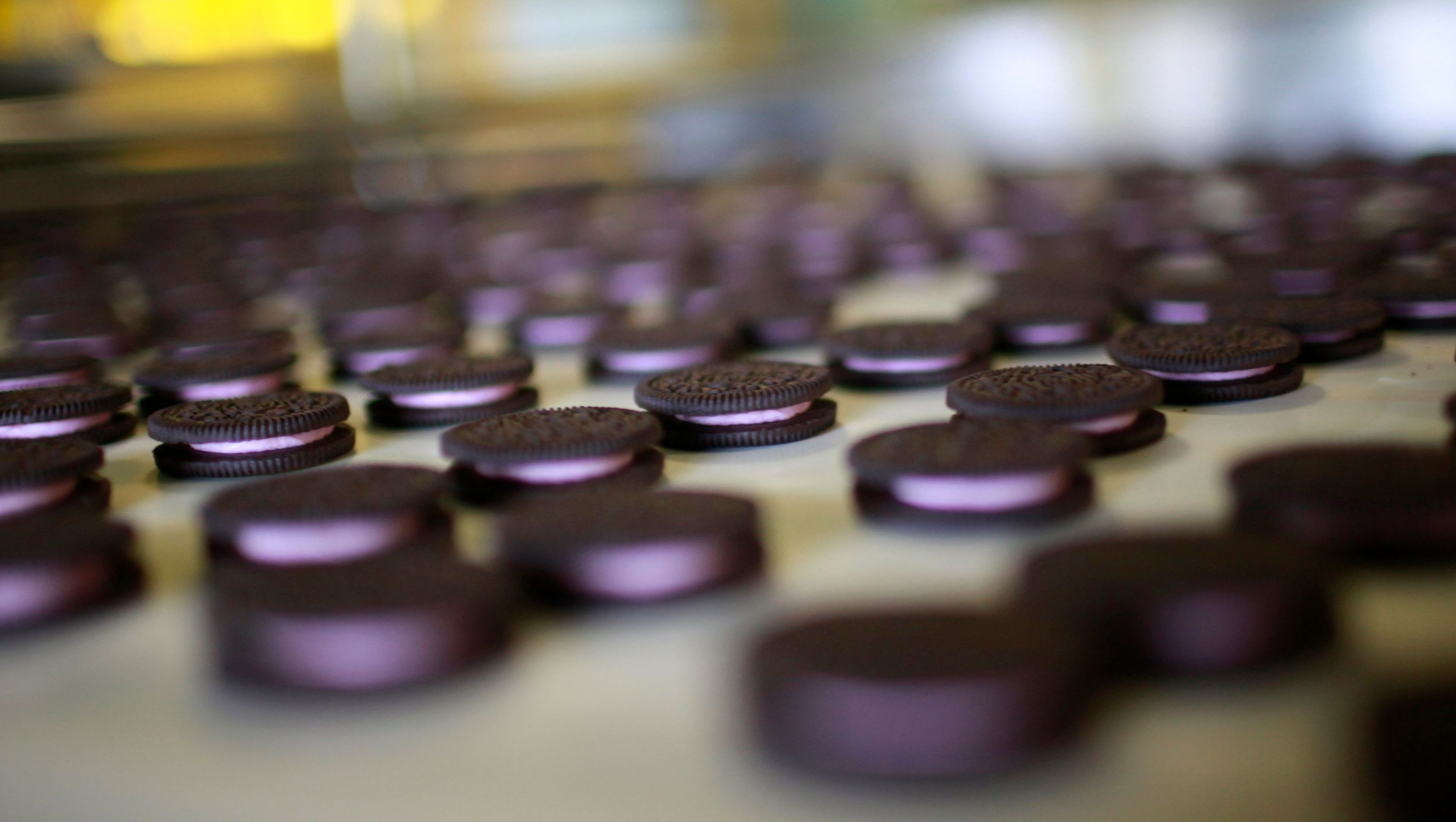 "Freshly-baked Oreo cookies pass along a conveyor belt at a Kraft Foods' factory in Suzhou, Jiangsu province May 30, 2012. Investment may be powering the Chinese economy but experiments like Oreo's gum cookie, a cookie with a glob of gum sandwiched neatly between a pair of Oreo's iconic dark chocolate biscuits instead of the creamy white ""stuff"", which for better or worse never made it to store shelves, are a reminder that consumption is rising sharply. That means it is vital for food companies to get the right products into the market, particularly with demand dimming in the United States and Europe. Picture taken May 30, 2012."