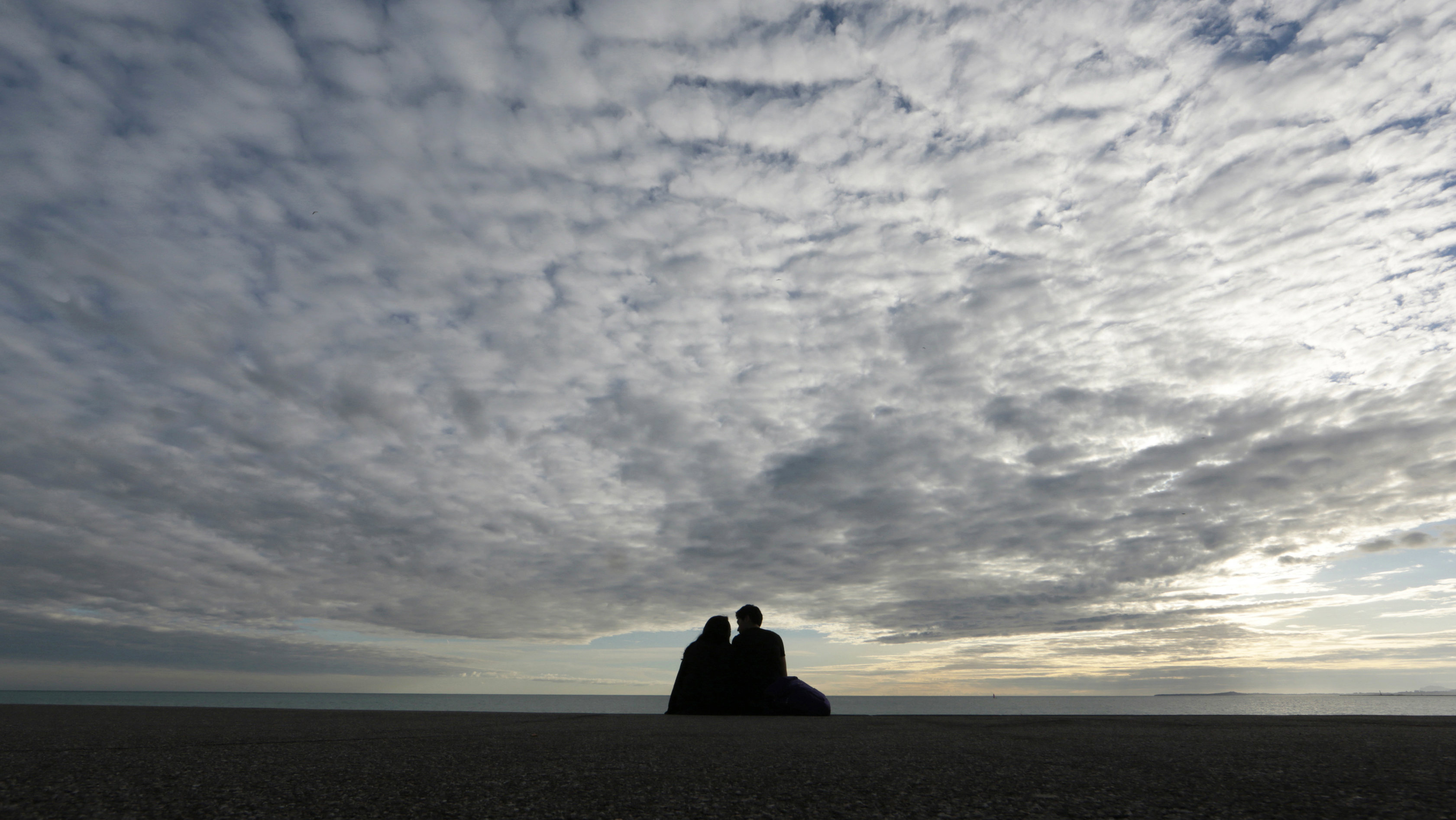 Craigslist Confessional: A couple is seen in silhouette under a partly cloudy sky as they sit along the Mediterranean Sea beach front on the Promenade Des Anglais in Nice December 2, 2014.