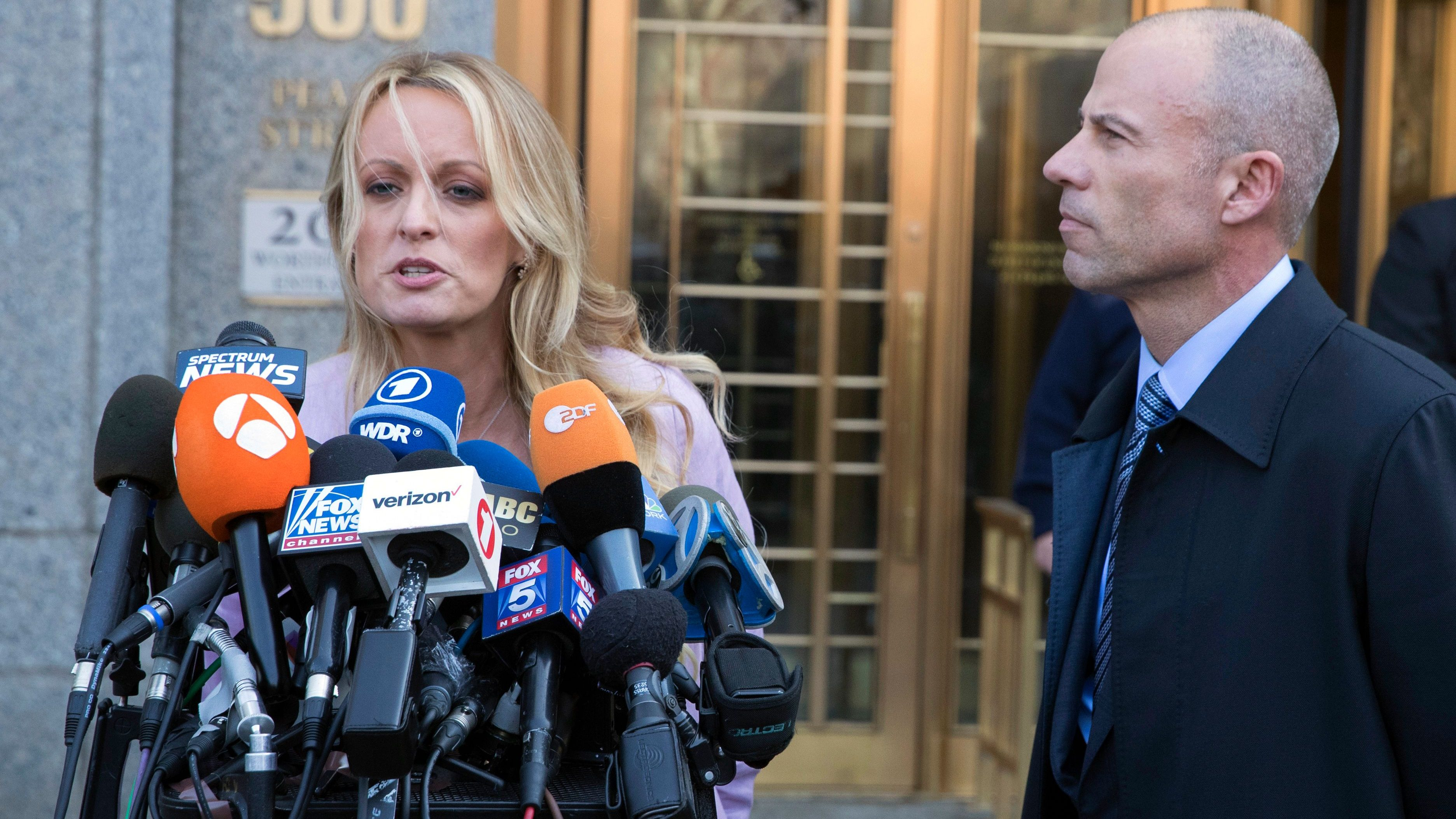 Adult film actress Stormy Daniels, left, speaks as her lawyer Michael Avenatti listens outside federal court, Monday, April 16, 2018, in New York. (AP Photo/Mary Altaffer)