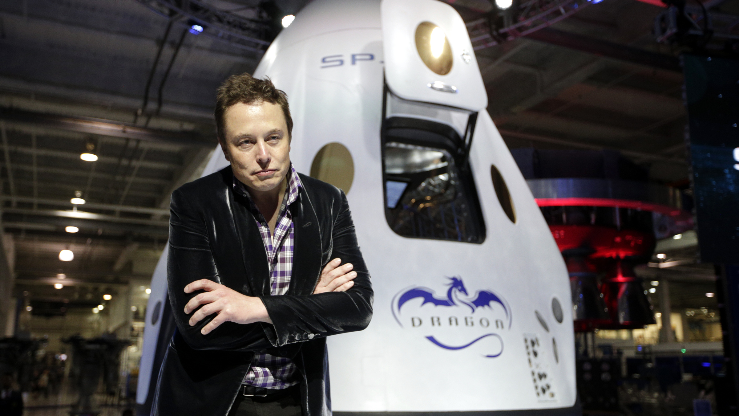 "In this Thursday, May 29, 2014 file photo, Elon Musk, CEO and CTO of SpaceX, listens to a question during a news conference in front of the SpaceX Dragon V2 spacecraft, designed to ferry astronauts to low-Earth orbit, at the headquarters in Hawthorne, Calif. The capsule was named for ""Puff the Magic Dragon,"" a jab at those who scoffed when Musk founded the company in 2002 and set the space bar exceedingly high. SpaceX went on to become the first private company to launch a spacecraft into orbit and return it safely to Earth in 2010."