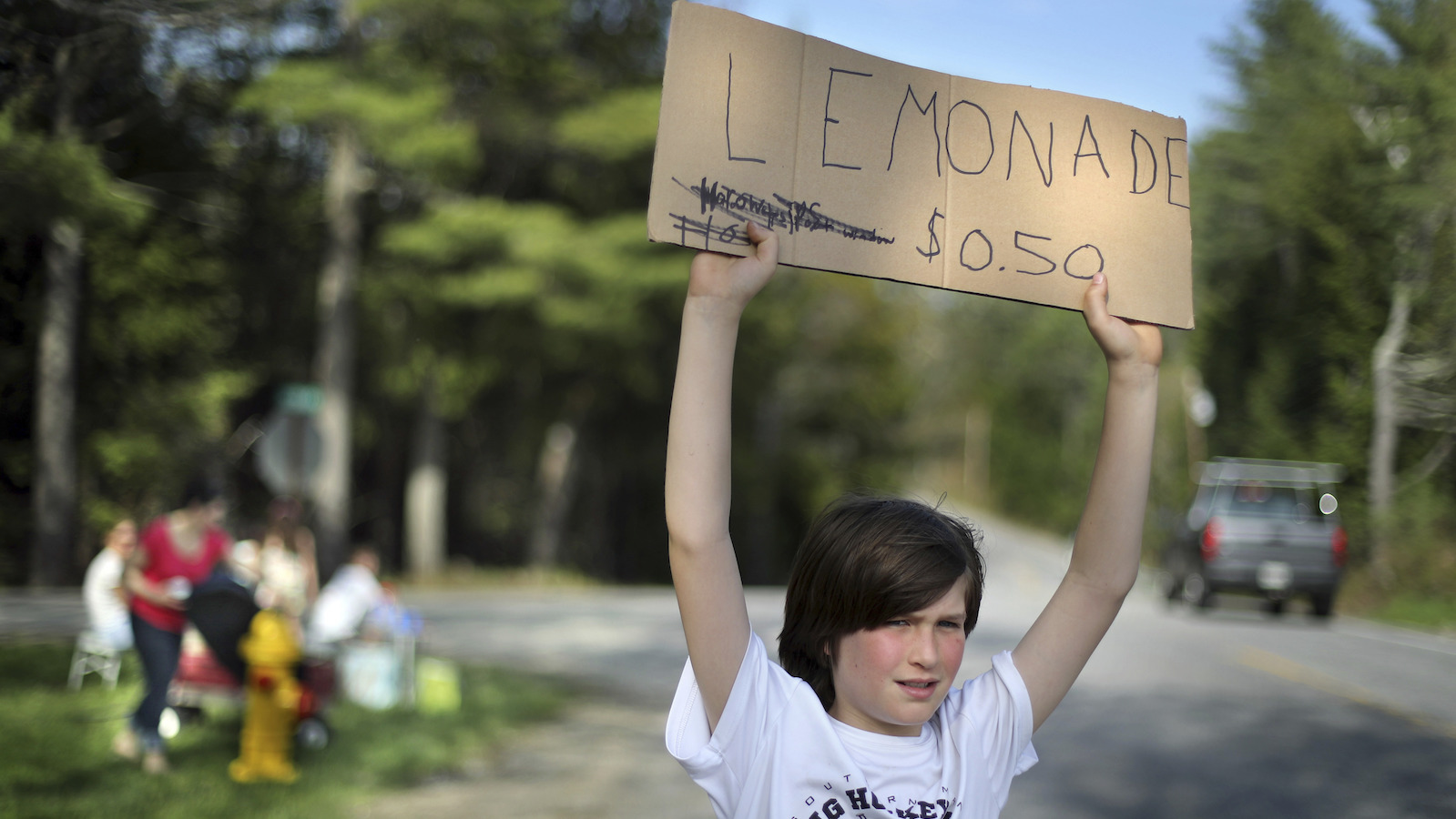 Cooper Jacobs tries to attract motorist's to his family's lemonade stand in Freeport, Maine.