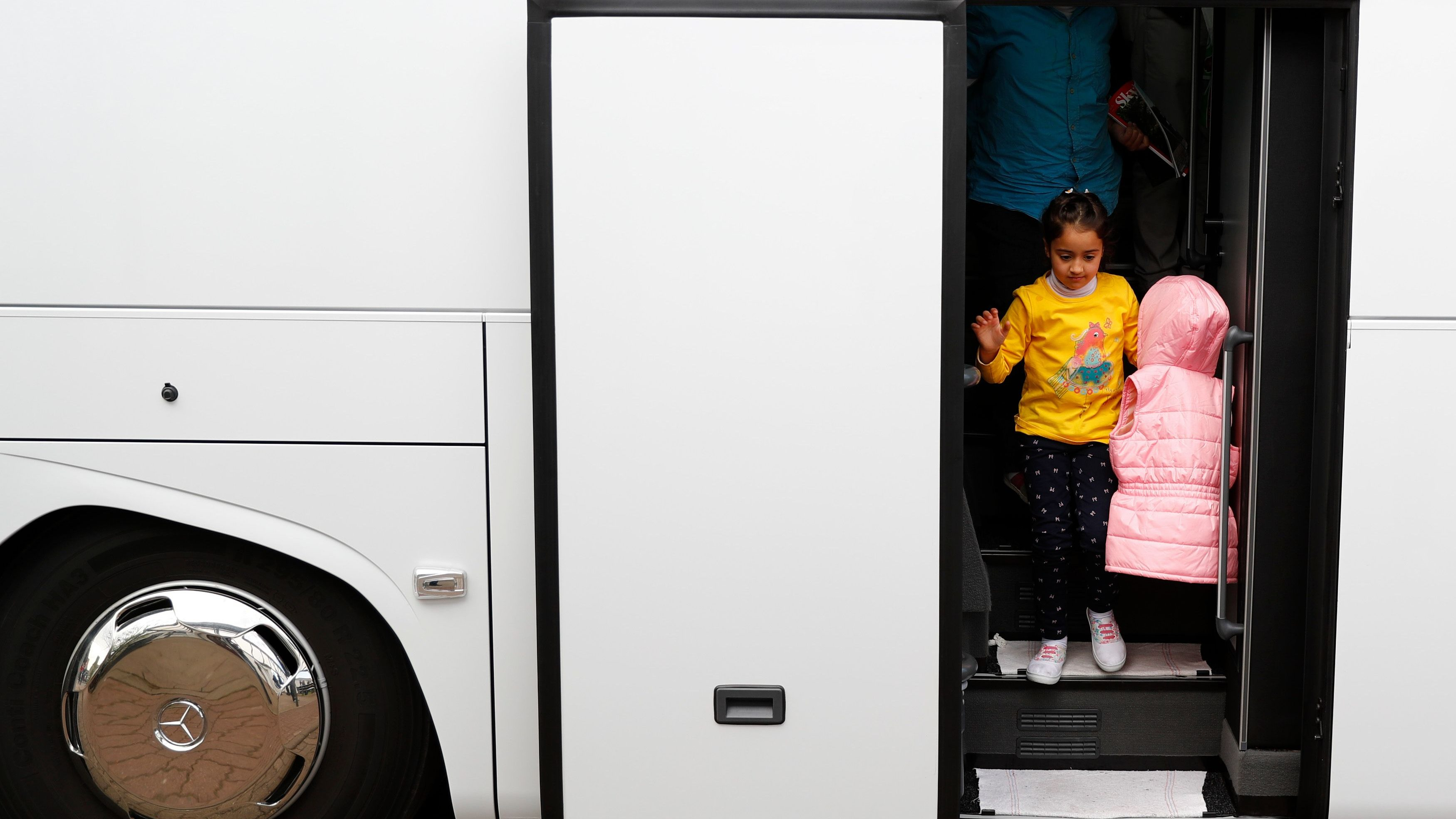 Syrian refugees disembark from a bus on arrival at the camp for refugees and migrants in Germany
