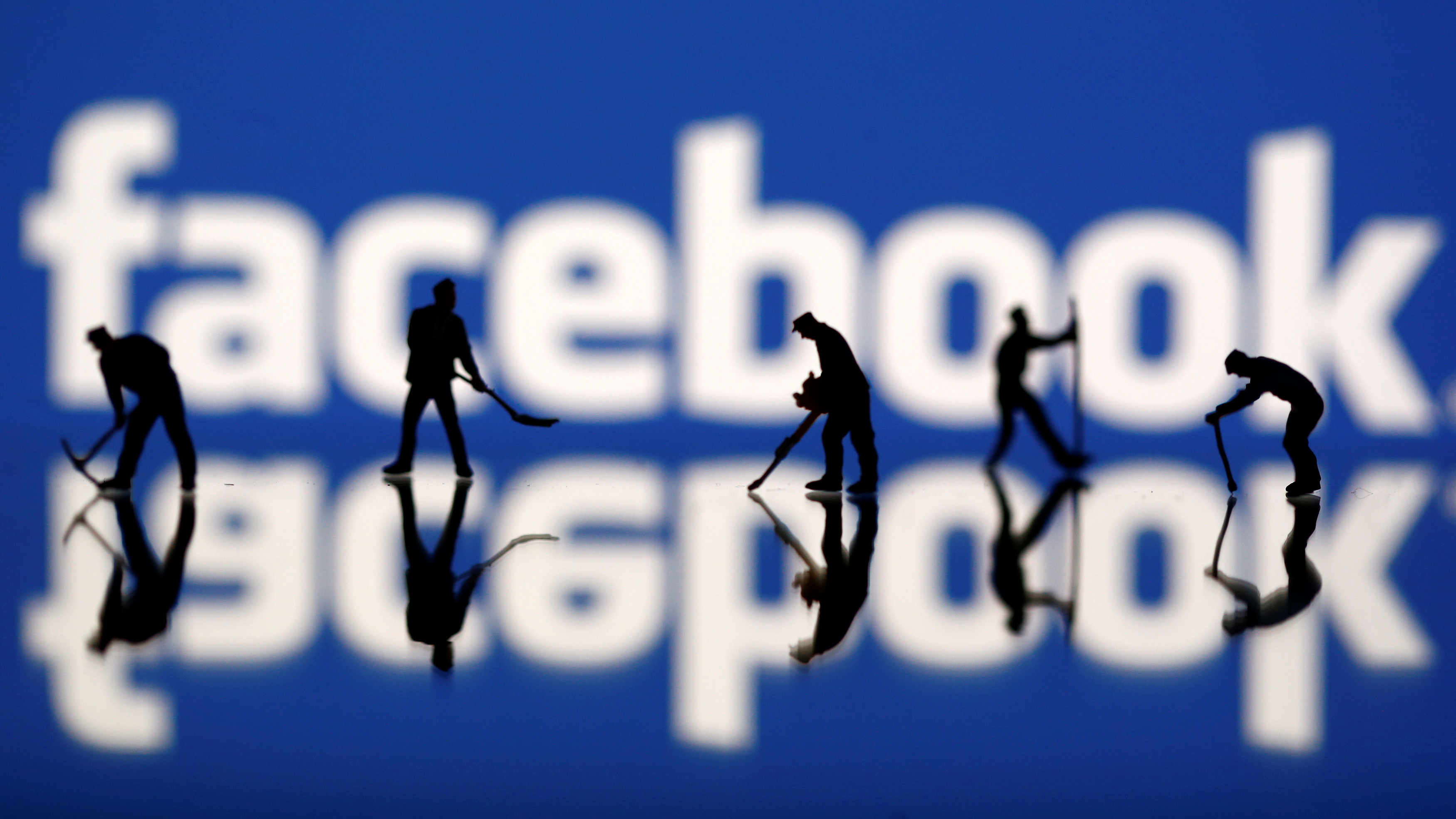 Figurines are seen in front of the Facebook logo in this illustration taken March 20, 2018. REUTERS/Dado Ruvic - RC190C231590