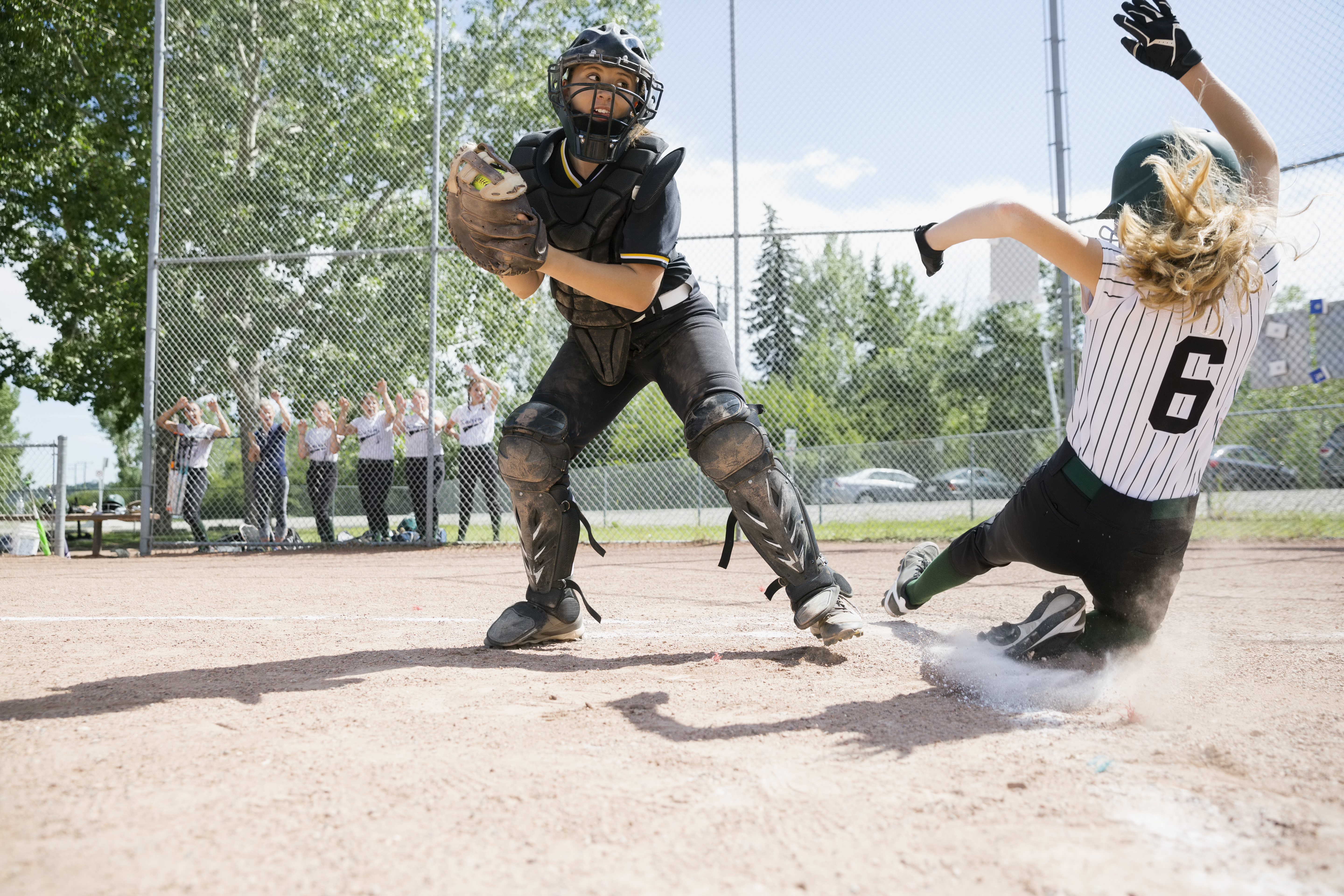 woman sliding into home base playing baseball