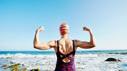 woman flexing muscles at the beach
