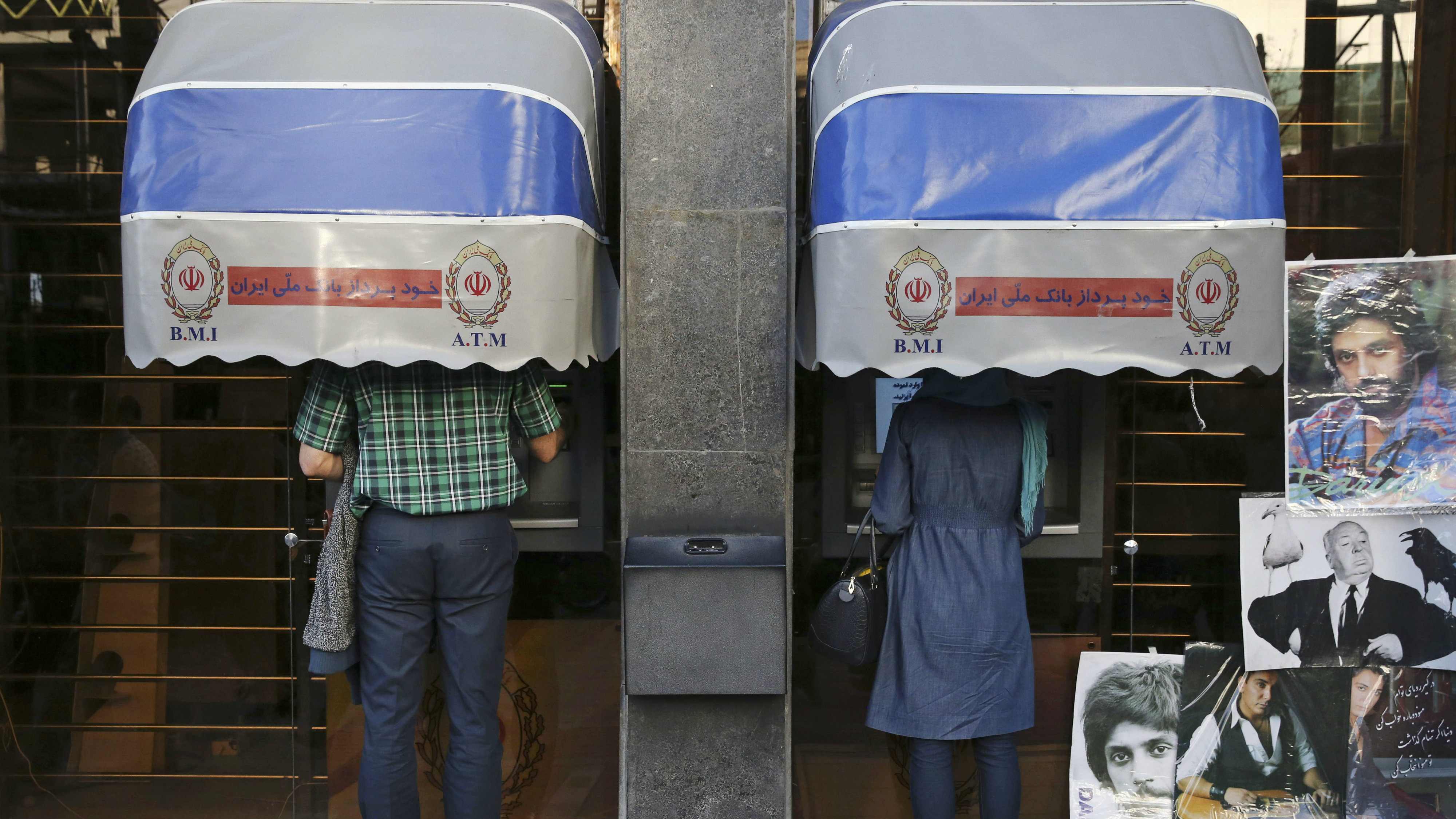 In this April 4, 2015 file photo, Iranians use ATM machines of Bank Melli Iran in downtown Tehran, Iran. Iranian media are saying the country's banks will begin issuing credit cards for the first time in decades. Reports by several newspapers, including the daily Donya-e-Eqtesad, Monday, Sept. 26, 2016 said the cards will be for domestic use only and do not involve any sort of partnership with a major international credit card company. So far, Iranian banks have only issued debit and prepaid cards.