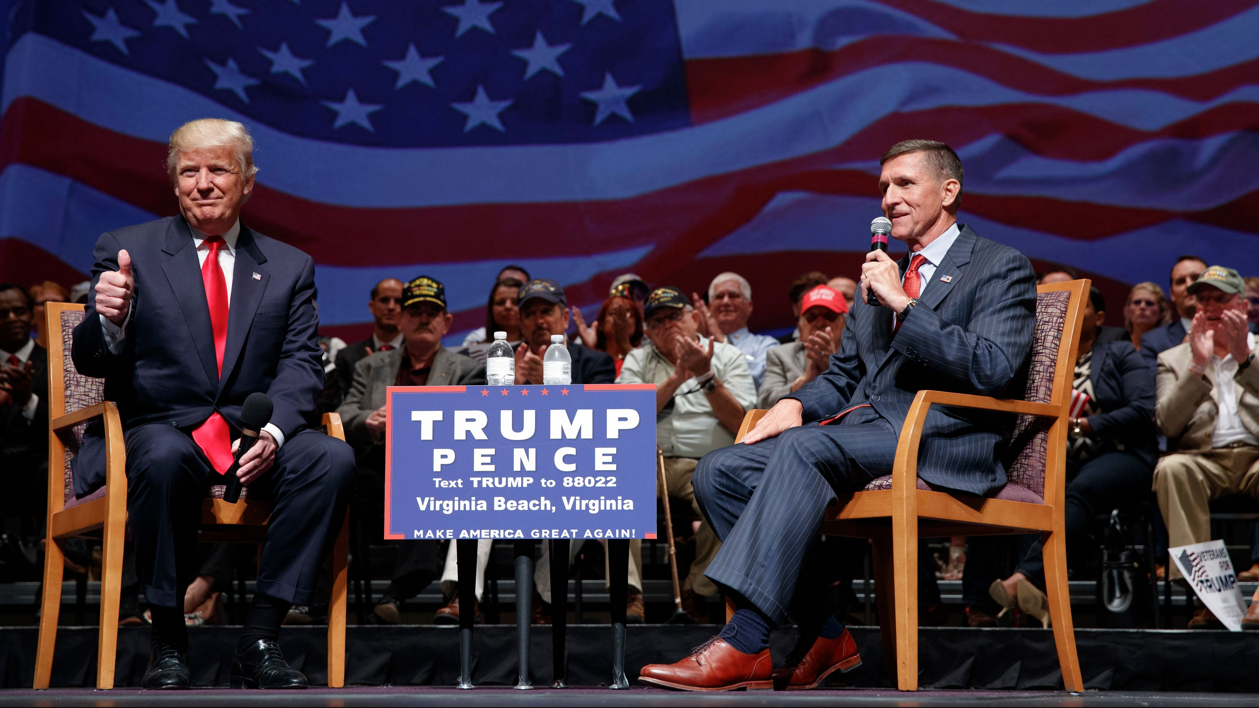Republican presidential candidate Donald Trump gives a thumbs up as he speaks with retired Lt. Gen. Michael Flynn during a town hall, Tuesday, Sept. 6, 2016, in Virginia Beach, Va. (AP Photo/Evan Vucci)