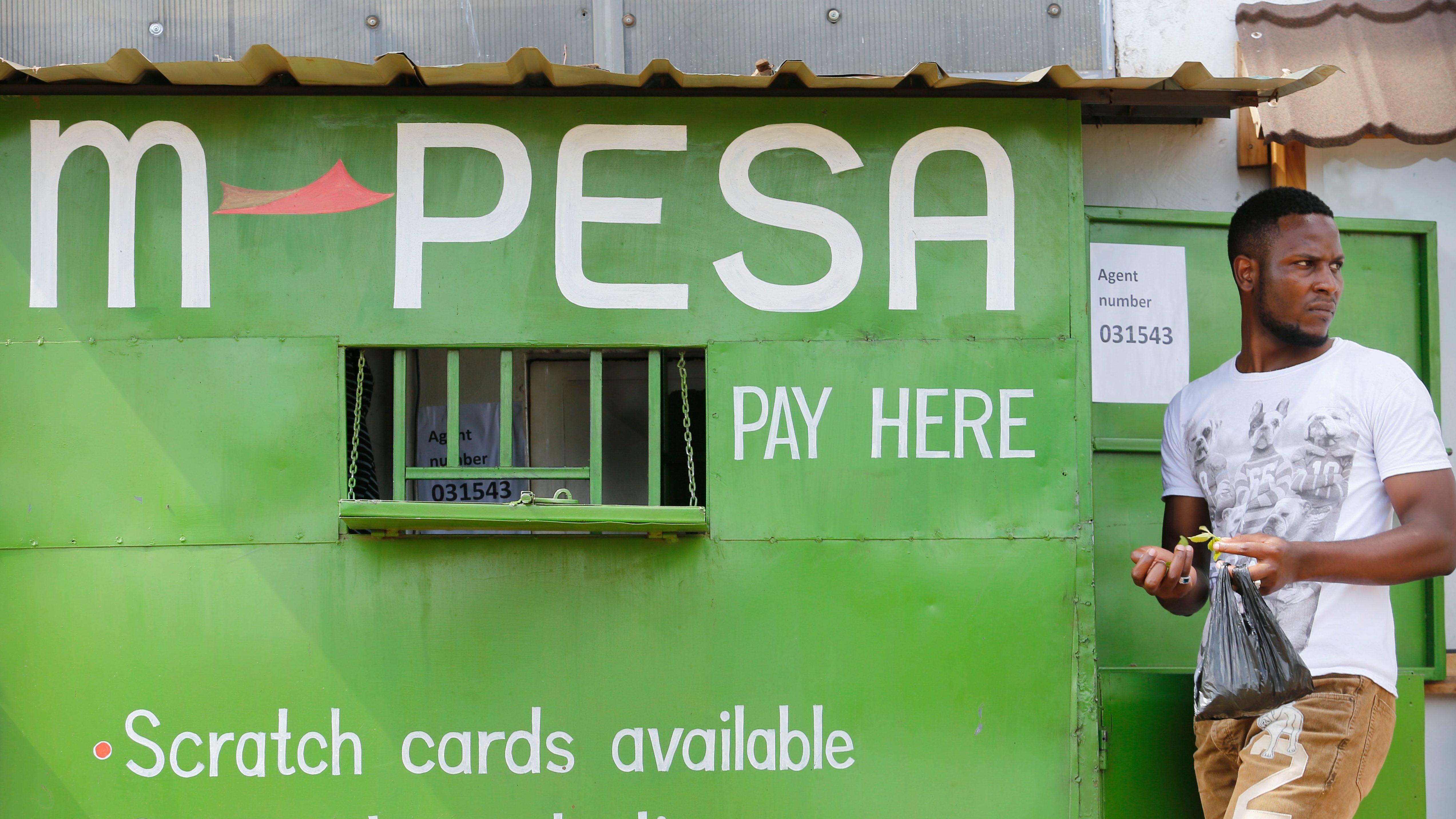 A man stands next to an M-Pesa service outlet in Kibera slum, Nairobi, Kenya, 01 December 2016. M-Pesa is a mobile money transfer platform offered by Kenya's mobile network operator Safaricom.