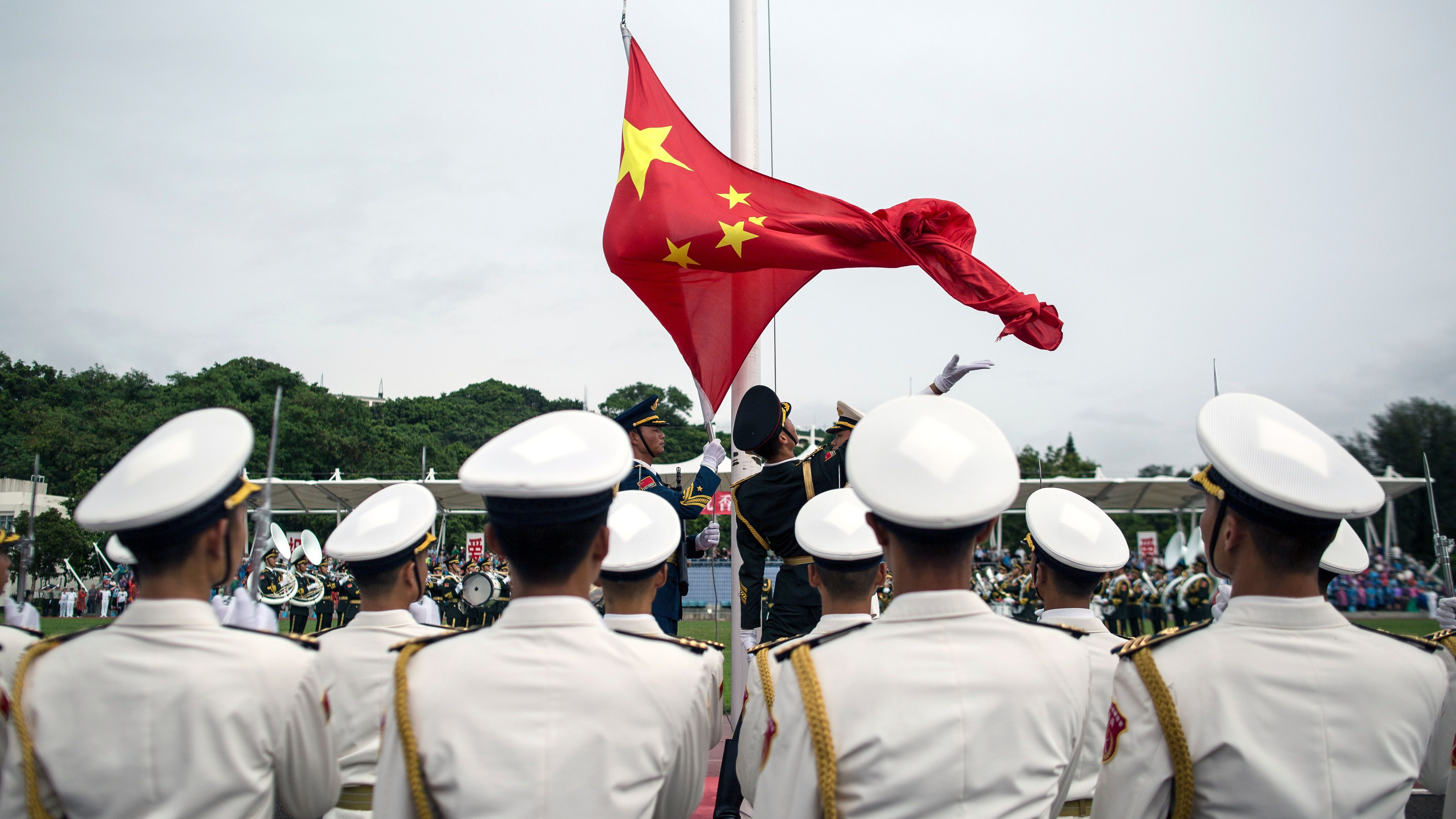 People's Liberation Army (PLA) soldiers participate in a flag raising ceremony during an open day at the PLA navy base in Hong Kong, China, 08 July 2017. The Hong Kong Garrison of the Chinese People's Liberation Army held an open day a day after the Liaoning, the first aircraft carrier commissioned into China's military, arrived in the city. The People's Liberation Army Forces in Hong Kong comprises around 6,000 personnel.