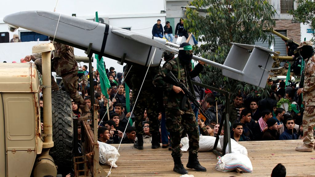 Palestinian members of al-Qassam Brigades, the armed wing of the Hamas movement, display a home-made drone during a military parade marking the 27th anniversary of Hamas' founding, in Gaza City December 14, 2014.