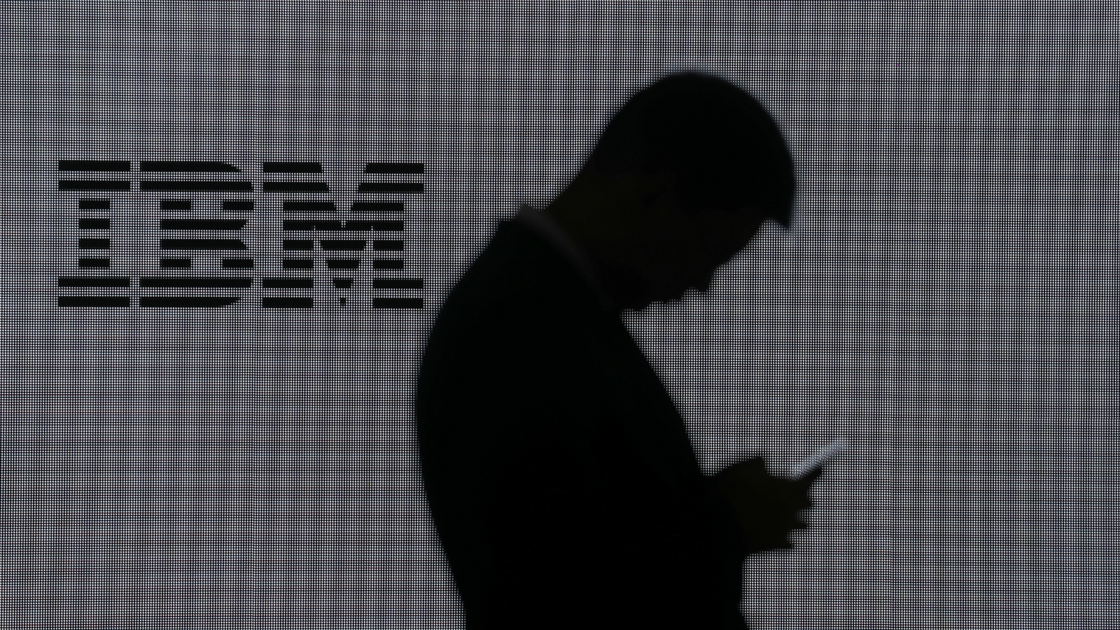 A man checks his mobile phone outside IBM's booth at the Mobile World Congress in Barcelona, Spain, February 28, 2018. REUTERS/Sergio Perez