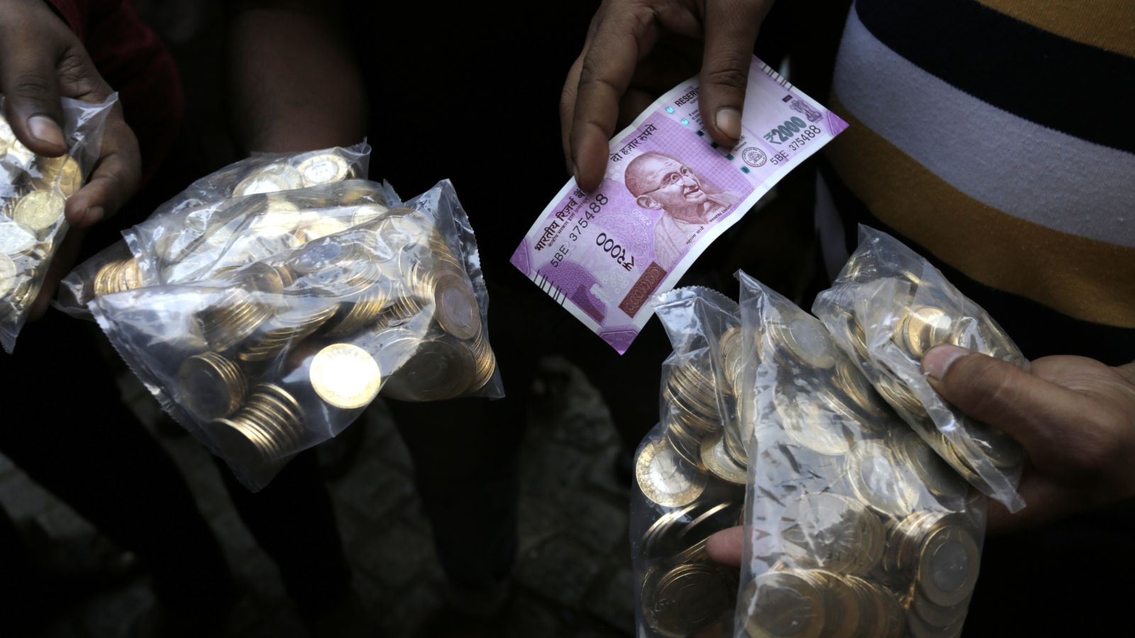 An Indian shows a new Rupees 2000 currency note and coins of Rupees 10 he received in exchange of discontinued currency outside the Reserve Bank of India in Kolkata, India, Wednesday, Nov. 16, 2016. India announced a week ago that it was withdrawing 500 and 1,000 rupee notes as legal tender to fight corruption and tax evasion. However, people are allowed a onetime swap of 4,000 rupees ($59) at any bank in exchange for smaller notes to meet immediate needs.