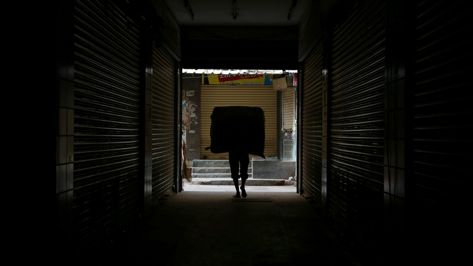 An Indian worker carries a load through a dark alley of a wholesale market on International Labor Day or May Day in Bangalore, India, Thursday, May 1, 2014.