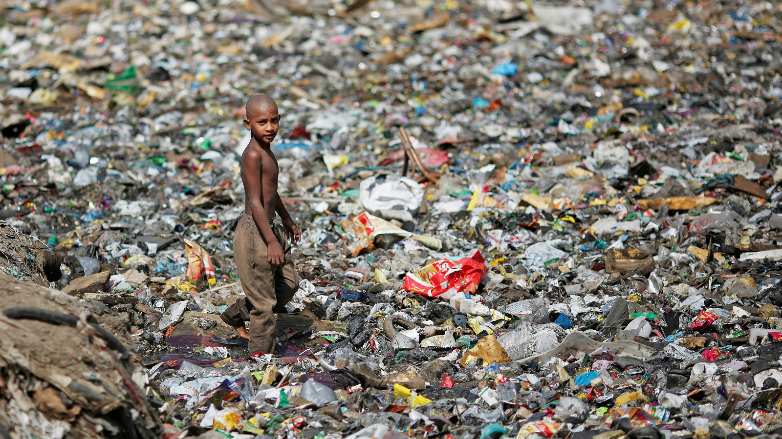A boy walks on a pile of garbage covering a drain in New Delhi, India, April 23, 2018.