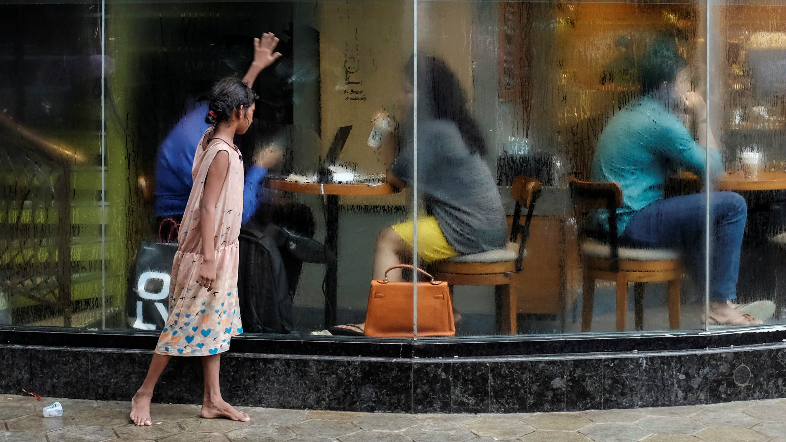 A homeless girl asks for alms outside a coffee shop in Mumbai, India, June 24, 2016.