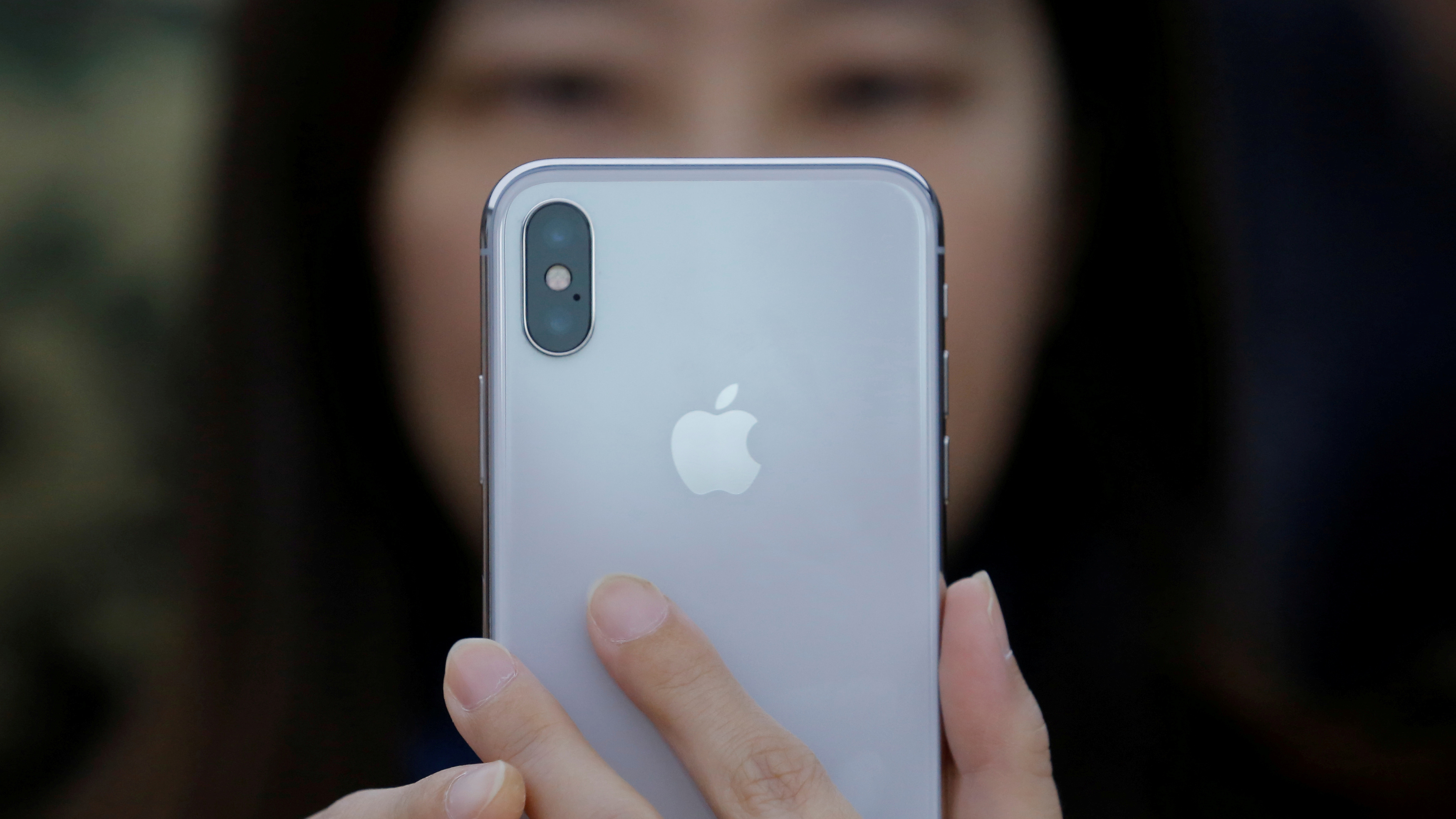 FILE PHOTO: A attendee uses a new iPhone X during a presentation for the media in Beijing, China October 31, 2017. REUTERS/Thomas Peter/File Photo - RC1C24F9CCE0