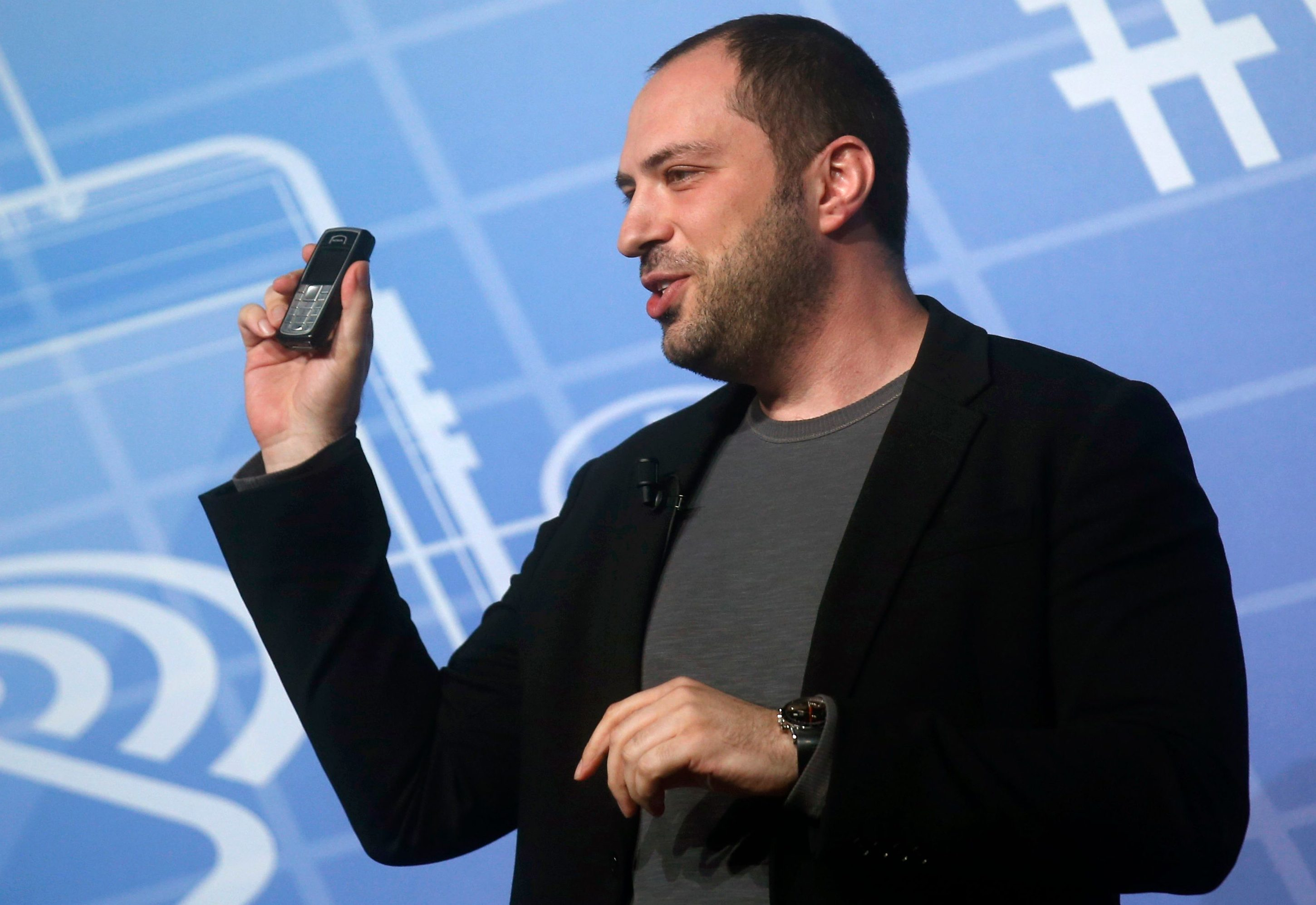 WhatsApp Chief Executive Officer and co-founder Jan Koum holds up a mobile phone as he delivers a keynote speech at the Mobile World Congress  in Barcelona February 24, 2014. The world's biggest messaging service WhatsApp will add voice calls to its product in the second quarter of this year, Koum said, days after its blockbuster $19 billion acquisition by Facebook.