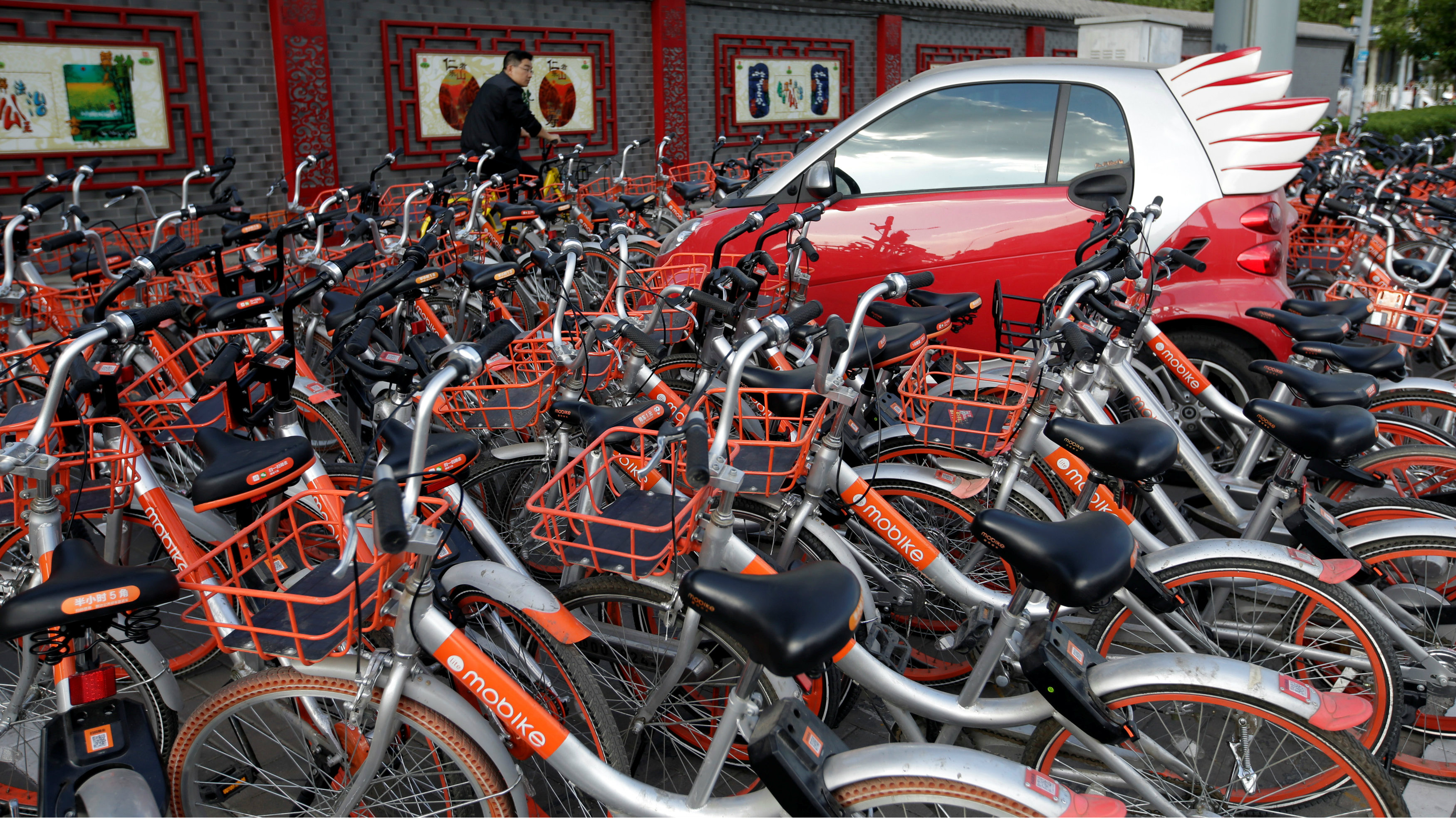 Mobike's shared bikes are parked around a car in Beijing, China