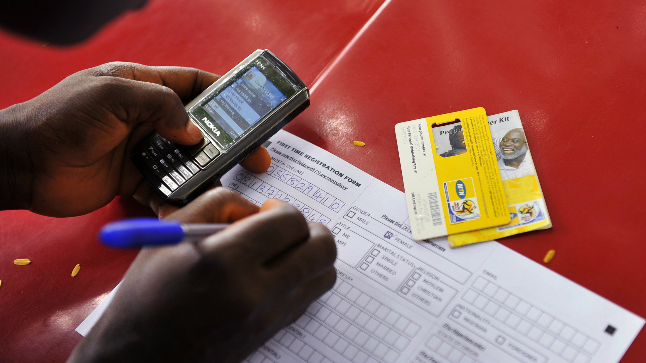 An official of MTN, a mobile telecommunications company, registers a SIM card as he attends to customers at a makeshift SIM card registration centre in Nigeria's capital Abuja August 3, 2010. The registration of new SIM cards is a recent move by the Nigeria Communications Commission to help crime prevention efforts in the country, local media reported.