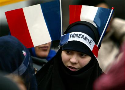 "A young muslim girl with two French flags and a headband which reads ""Fraternity"" pulled over her headscarf."