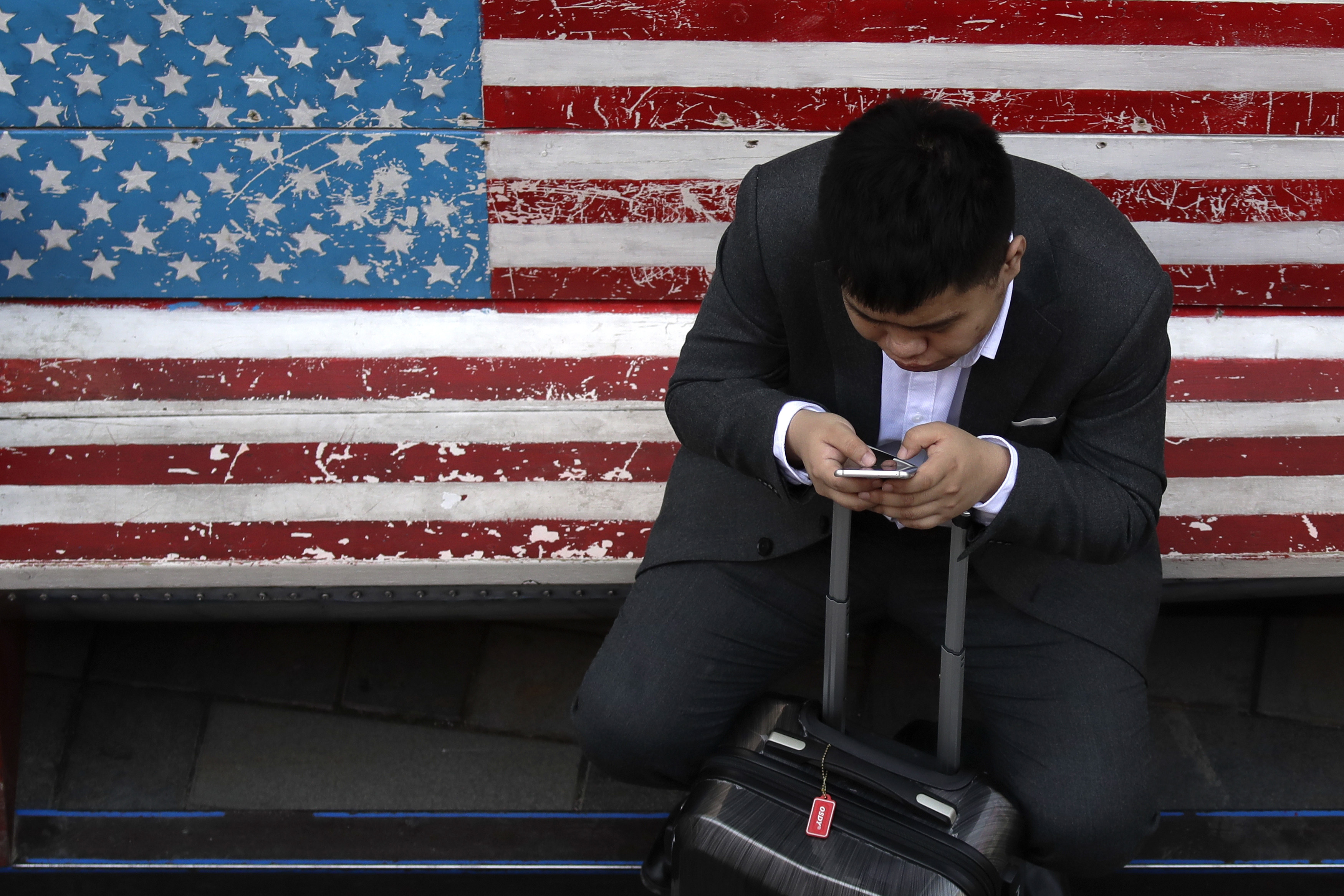 A man on a bench with an American flag checks his smartphone in Beijing.