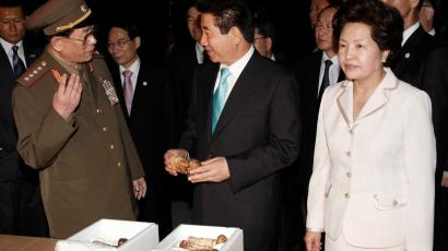 South Korean President Roh Moo-hyun (C) and his wife Kwon Yang-sook (R) look on pine mushrooms, which are a present from North Korean leader Kim Jong-il, during their return from Pyongyang, at the Customs, Immigration and Quarantine (CIQ) office in Kaesong, North Korea, October 4, 2007. South Korean media questioned on Friday whether the two Koreas' summit pledge to seek a formal end to their 1950-53 war could be realised given Pyongyang's record of broken promises.