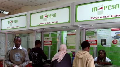 A man leaves an M-PESA booth after a money transaction in Nairobi May 12, 2009. Teaming up with Kenya Commercial Bank to let phone users who do not have bank accounts send each other money, M-PESA, the virtual cash network, hit on a formula that has attracted 6.5 million customers, or one in six Kenyans, in just over two years. Picture taken May 12, 2009.
