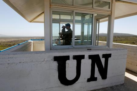 UN peacekeeping soldier, Australian Army Captain Morris uses binoculars from an observation tower located on the Israeli side of the 1973 Golan Heights ceasefire line with Syria