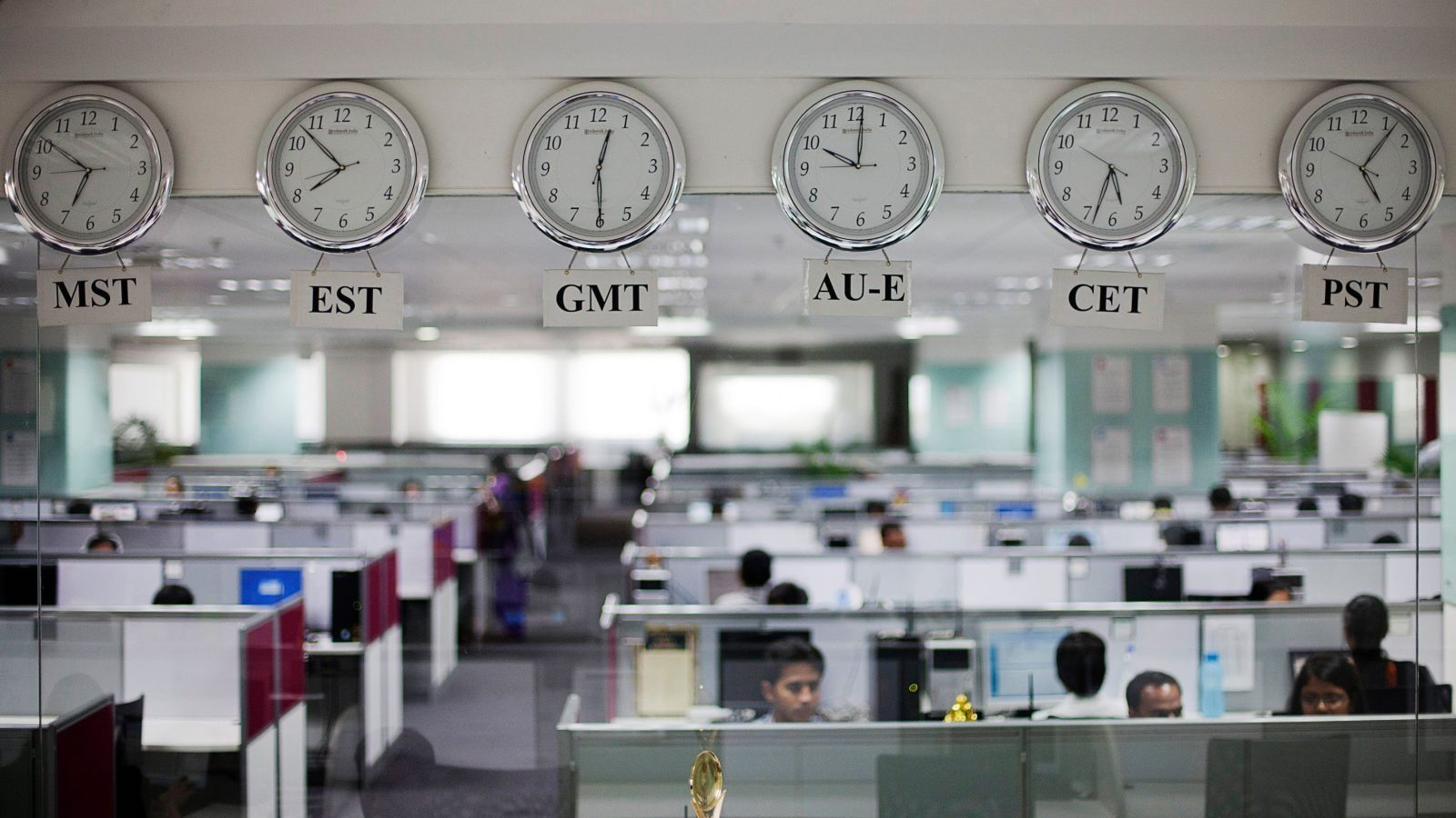 Workers are pictured beneath clocks displaying time zones in various parts of the world at an outsourcing centre in Bangalore, February 29, 2012. India's IT industry, with Bangalore firms forming the largest component, is now worth an annual $100 billion and growing 14 percent per year, one of the few bright spots in an economy blighted by policy stagnation and political instability. Picture taken on February 29, 2012.  To match Insight INDIA-OUTSOURCING/  REUTERS/Vivek Prakash (INDIA - Tags: BUSINESS EMPLOYMENT SCIENCE TECHNOLOGY) - GM1E8450SCD01