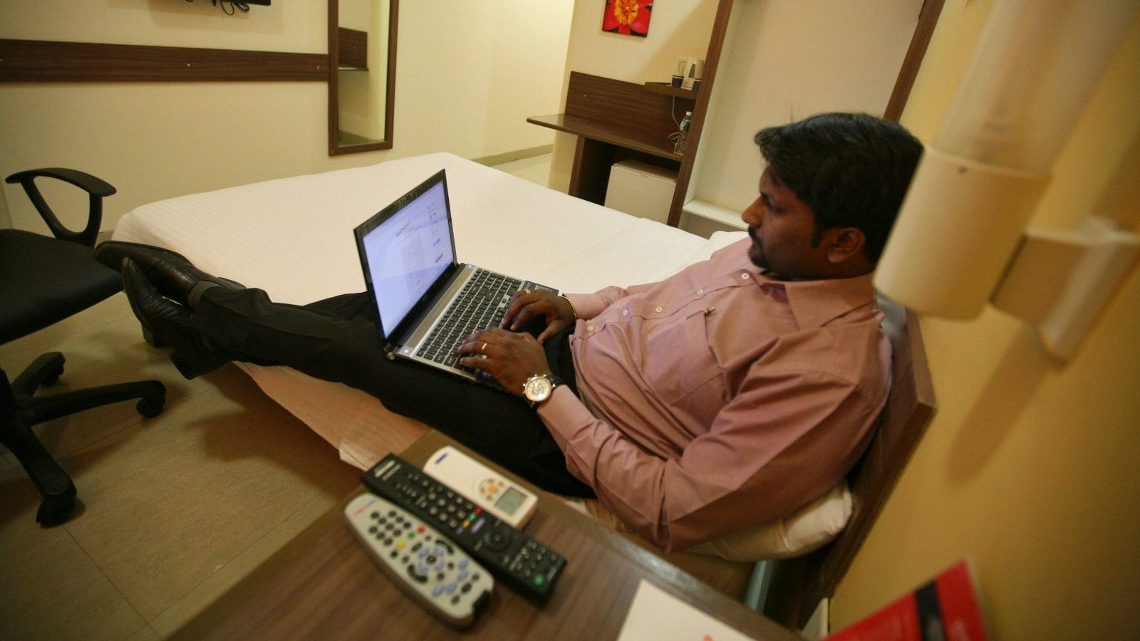 A guest works on a laptop inside his room at the Tata Group's Indian Hotels Co. Ginger chain in the western Indian city of Ahmedabad May 5, 2012. Rising spending by domestic travellers in India and Indonesia is prompting international hoteliers to build budget and mid-scale brands in the world's second and fourth largest populations. Ginger, run by the Tata Group's Indian Hotels Company, owner of Taj hotels, has 24 budget hotels in India with plans to grow to 75 hotels over the next four years. Picture taken May 5, 2012. REUTERS/Amit Dave (INDIA - Tags: BUSINESS TRAVEL SOCIETY) - GM2E86F0OA301