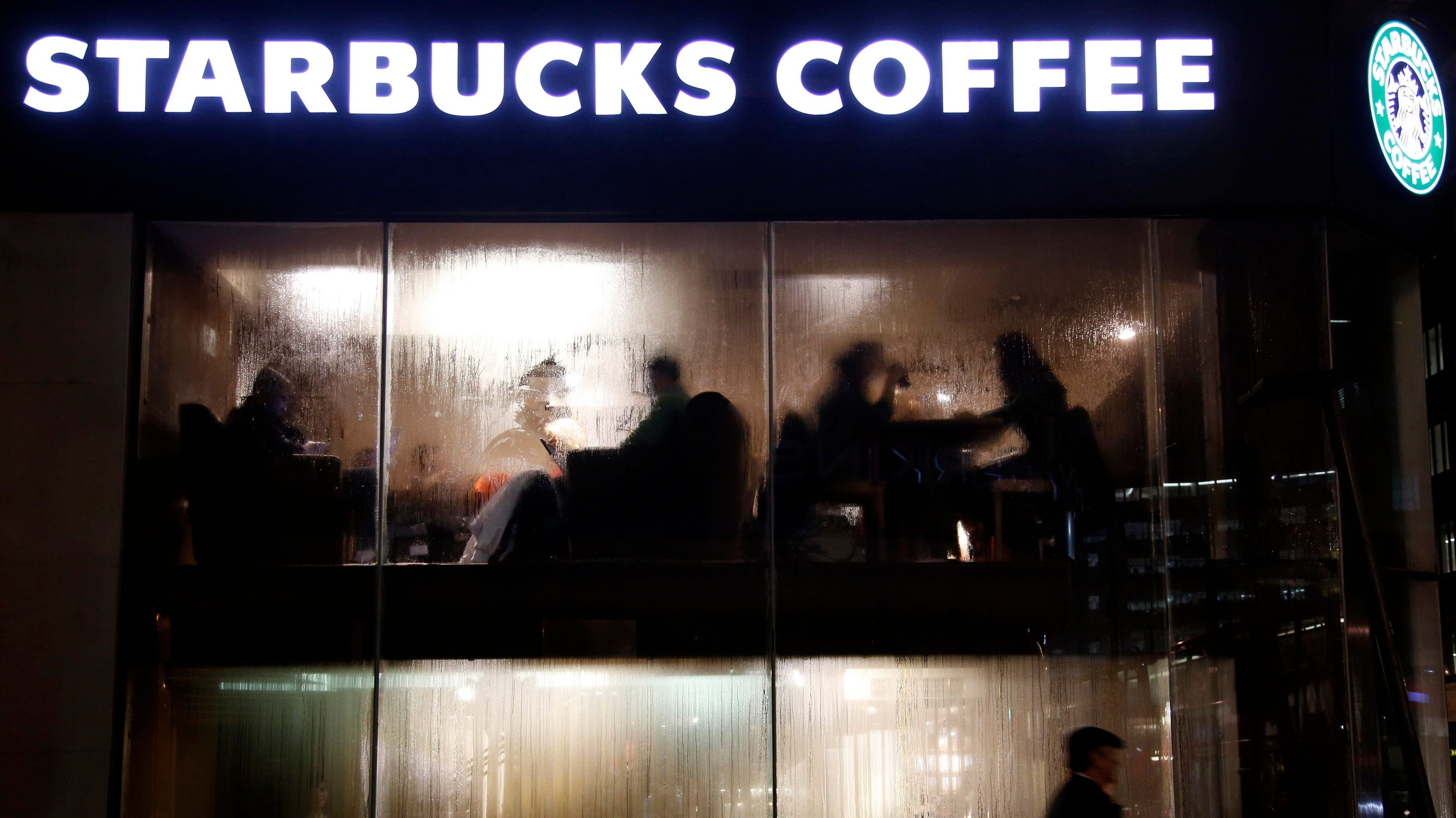 Customers are seen behind the steamy windows of a Starbucks coffee house in central London.