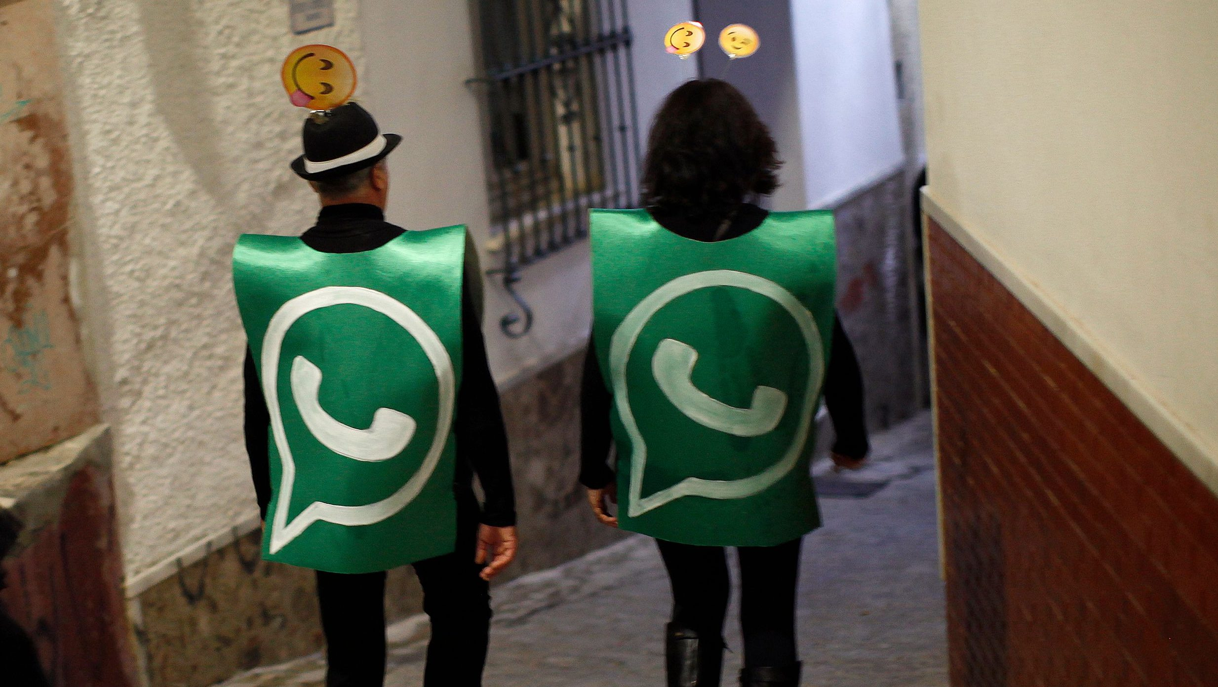 Revellers dressed up as dancers of 'Black Swan' check their mobile phones next to revellers dressed up as a Whatsapp logo as they take part in New Year's celebrations in Coin, near Malaga, southern Spain, early January 1, 2015. Villagers and revellers dressed up in funny costumes to take part in the New Year's celebration. REUTERS/Jon Nazca (SPAIN - Tags: SOCIETY ANNIVERSARY TPX IMAGES OF THE DAY) - GM1EB111IWI01