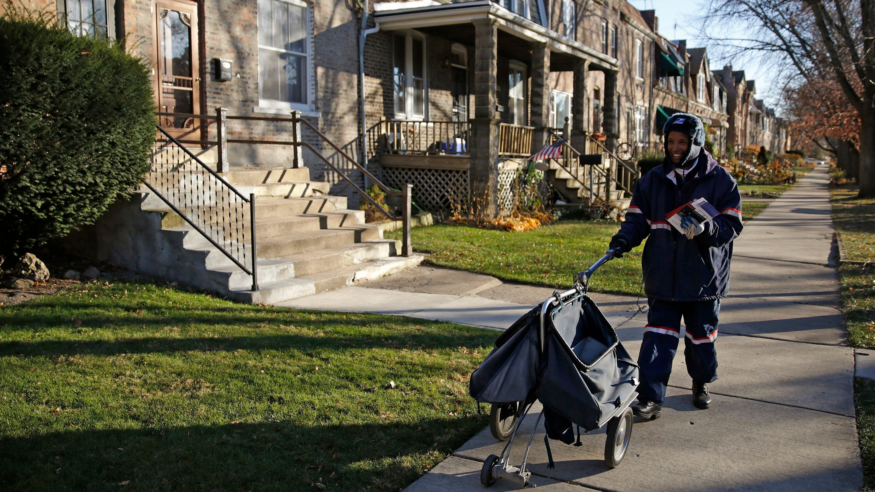 Mail carrier Marissa Ogletree delivers mail in the historic Pullman neighborhood in Chicago November 20, 2014. U.S. President Barack Obama is expected to announce the designation of the Pullman neighborhood as a national park on February 19, according to park advocates. The neighborhood's brick homes and ornate public buildings were built in the 1800s by industrialist George Pullman as a blue-collar utopia to house workers from his sleeper car factory. Picture taken November 20, 2014.    REUTERS/Andrew Nelles (UNITED STATES - Tags: SOCIETY POLITICS ENVIRONMENT) - TM3EABN1EM301