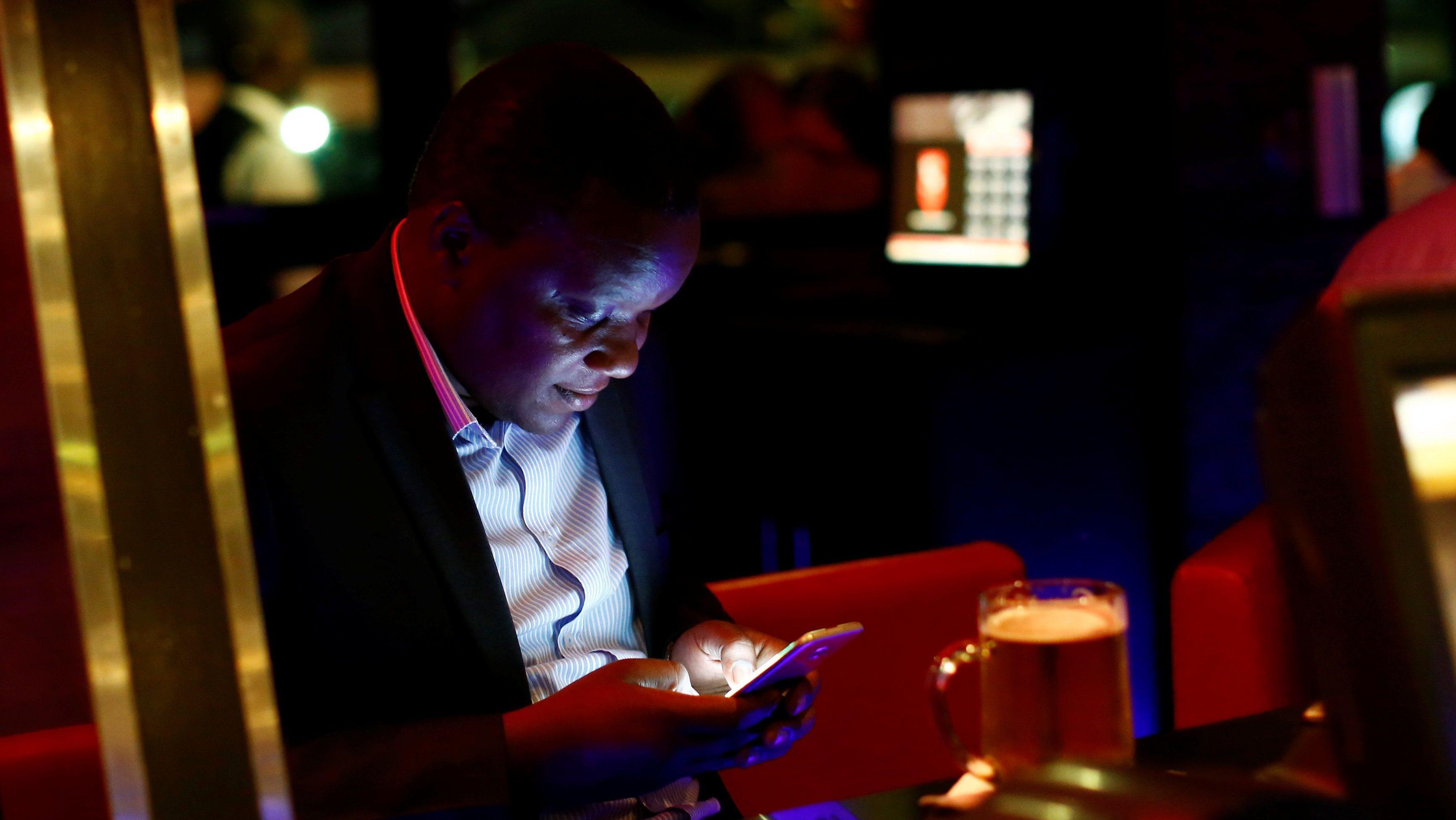 A man uses his mobile phone at the Brew Bistro & Lounge in Nairobi, Kenya, April 13, 2017.