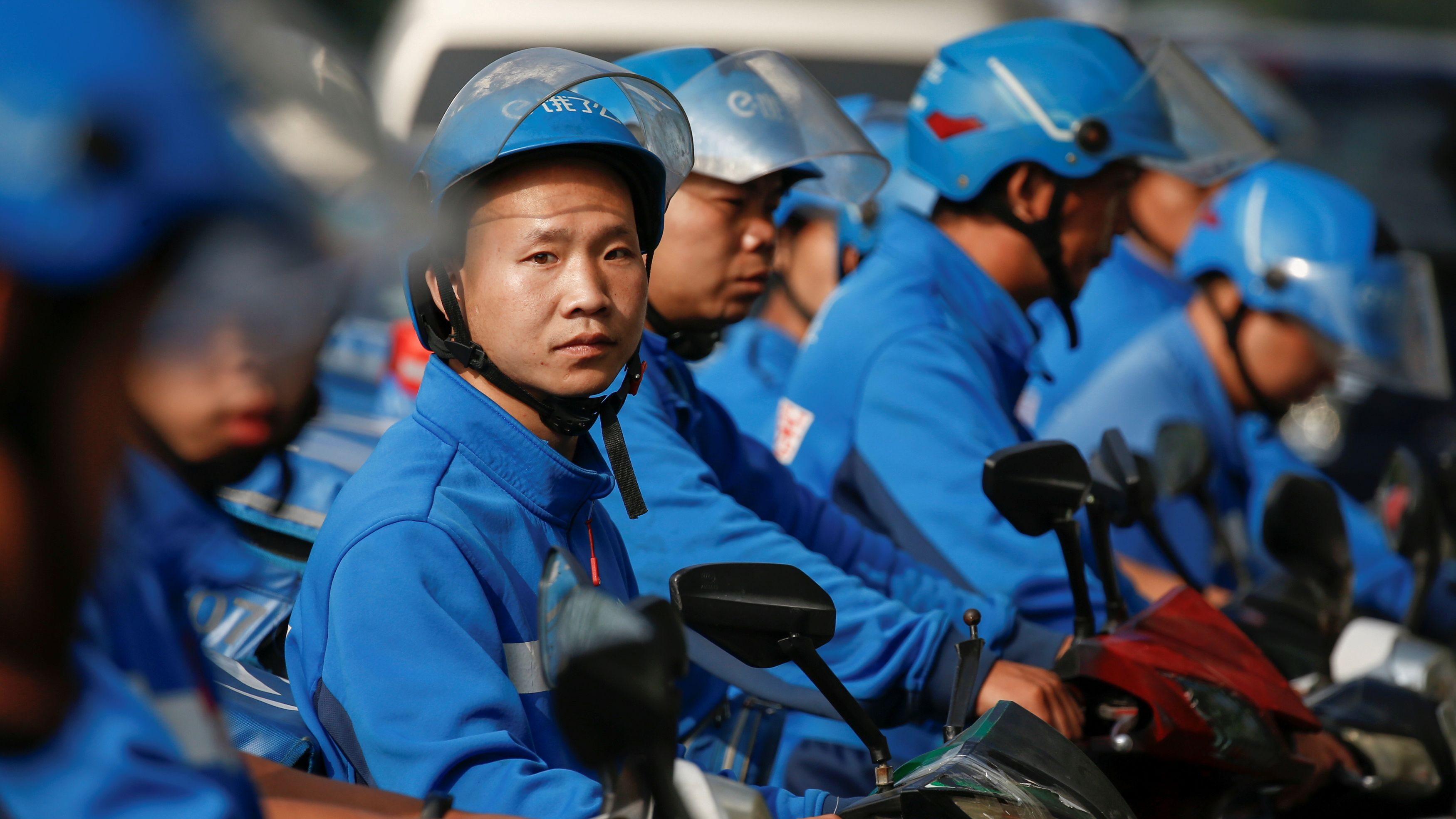 Drivers of the food delivery service Ele.me prepare to start their morning shift after an internal security check in Beijing, China, September 21, 2017. Picture taken September 21, 2017.