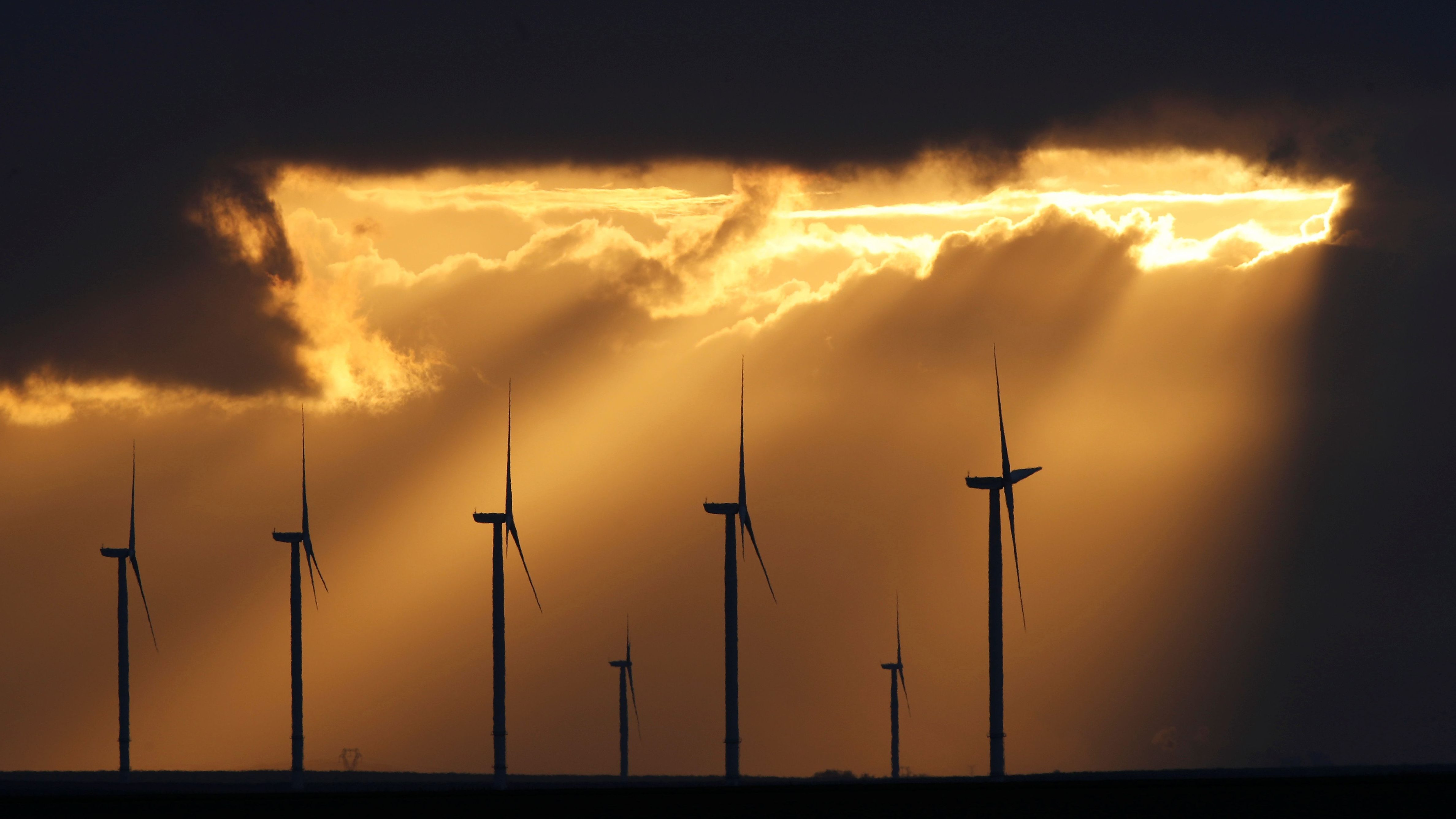 Power-generating windmill turbines are seen during sunset at a wind park near Reims, France, November 13, 2017. REUTERS/Christian Hartmann - RC1FEFD9C1F0