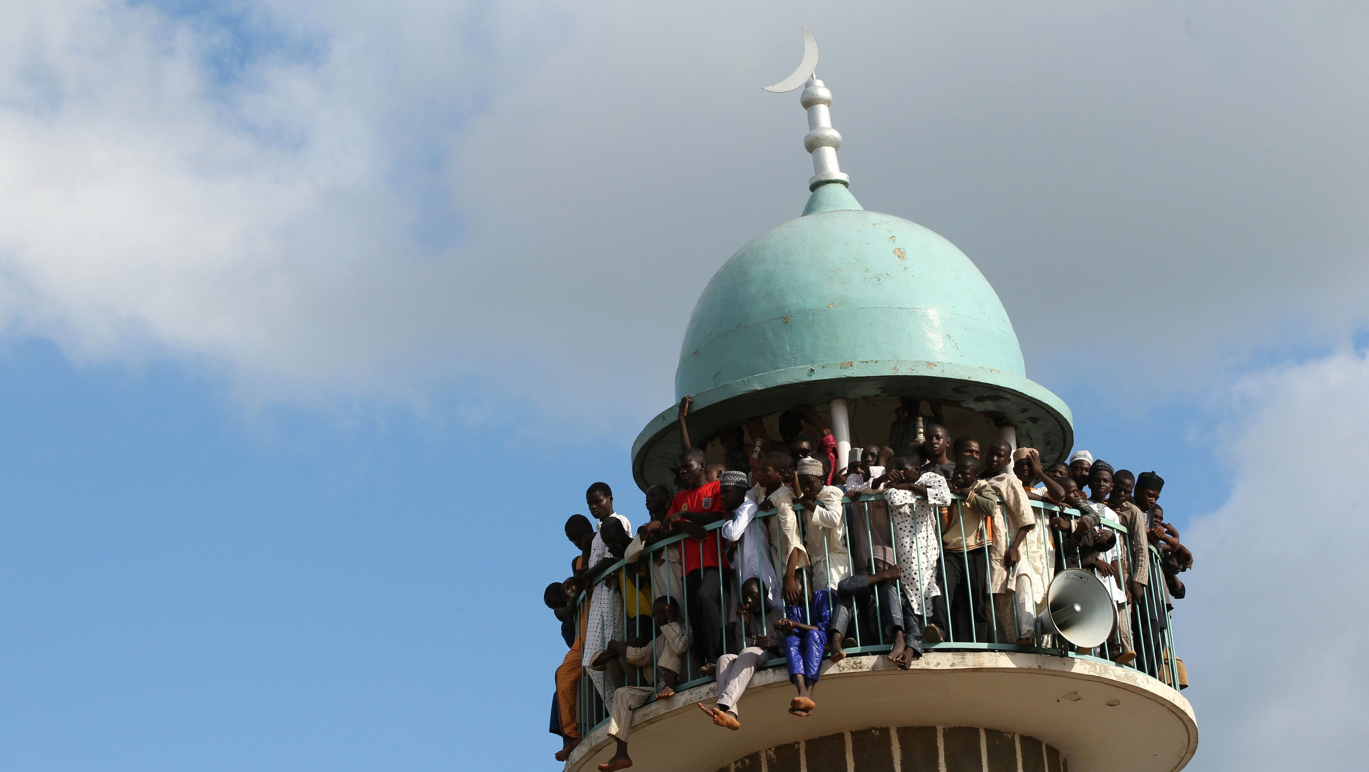 Spectators watch from a mosque minaret to try to get a better view of the Durbar festival parade in Zaria, Nigeria September 14, 2016. Picture taken September 14, 2016.