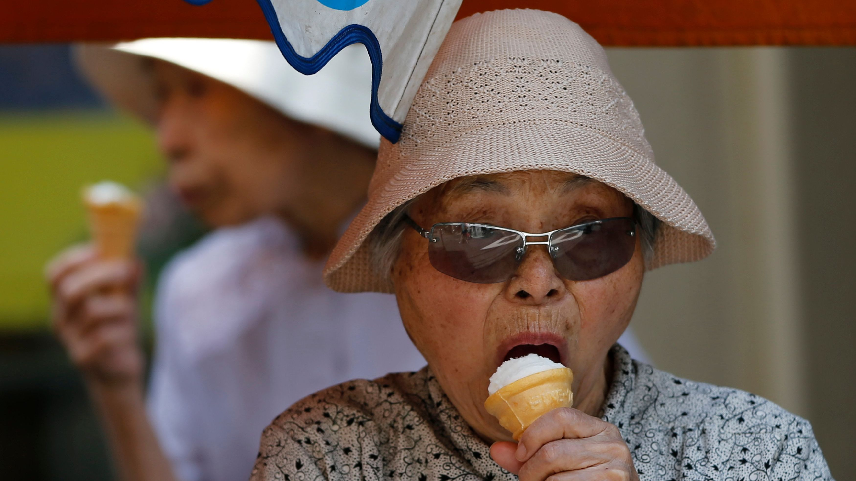 Elderly women eat ice-cream at Tokyo's Sugamo district, an area popular among Japanese elderly, in Tokyo