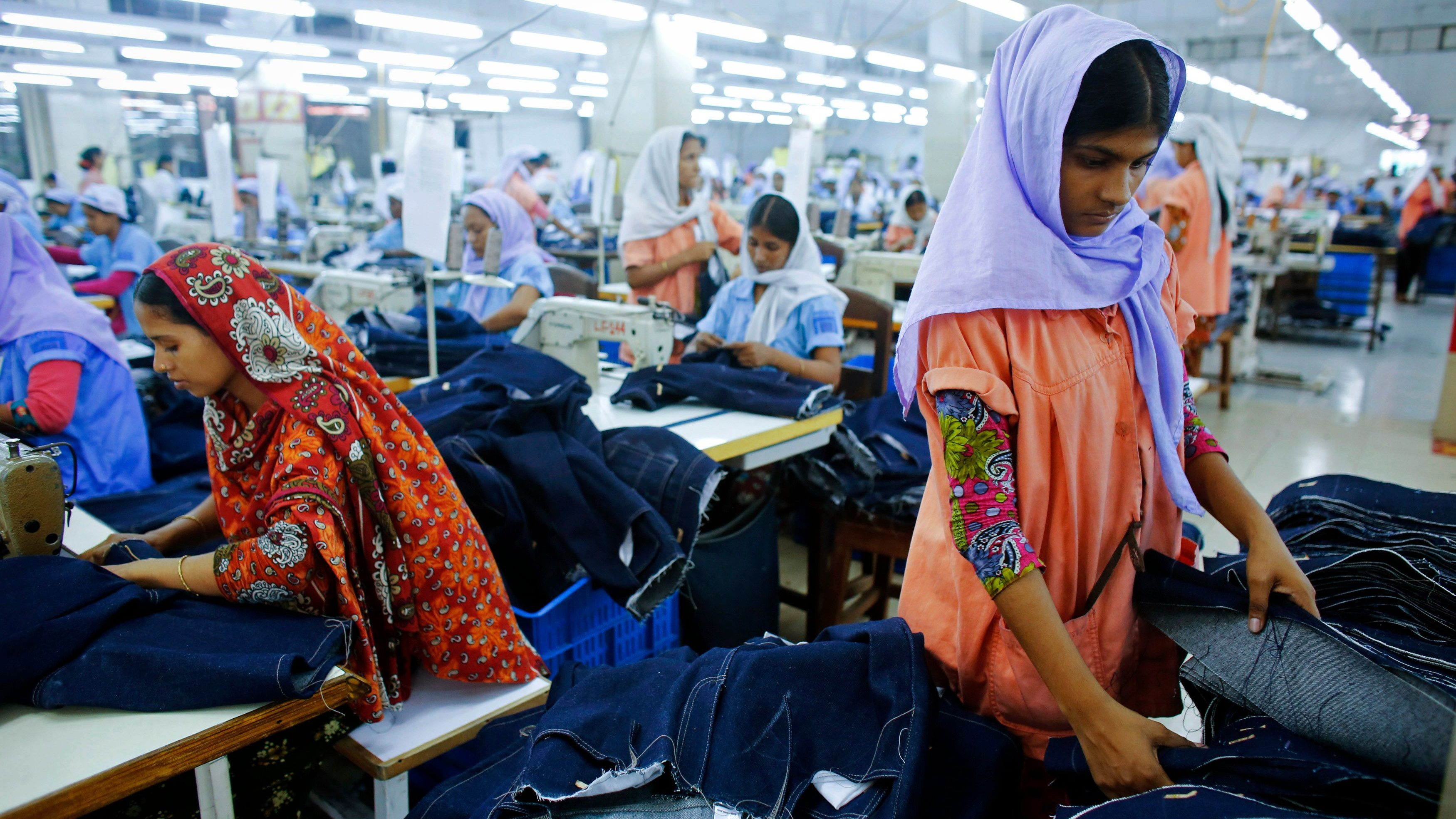 Workers sort clothes at a garment factory near the collapsed Rana Plaza building in Savar, Bangladesh June 16, 2013. The April 24 collapse of the Rana Plaza complex, built on swampy ground outside Dhaka with several illegal floors, killed 1,132 workers and focused international attention on sometimes lax safety standards in Bangladesh's booming garment industry. At least five different Bangladesh agencies have dispatched teams to start inspecting the country's thousands of garment factories, but there has been little coordination between them. More than four million people, mostly women, work in Bangladesh's clothing sector, which is the country's largest employment generator, with annual exports worth $21 billion. Picture taken June 16, 2013. REUTERS/Andrew Biraj  (BANGLADESH - Tags: BUSINESS INDUSTRIAL EMPLOYMENT SOCIETY)  ATTENTION EDITORS: PICTURE 01 OF 35 FOR PACKAGE 'INDUSTRY'S VICTIMS IN BANGLADESH'. TO FIND ALL IMAGES SEARCH 'INDUSTRY'S VICTIMS BIRAJ' - GM1E97R16OO01
