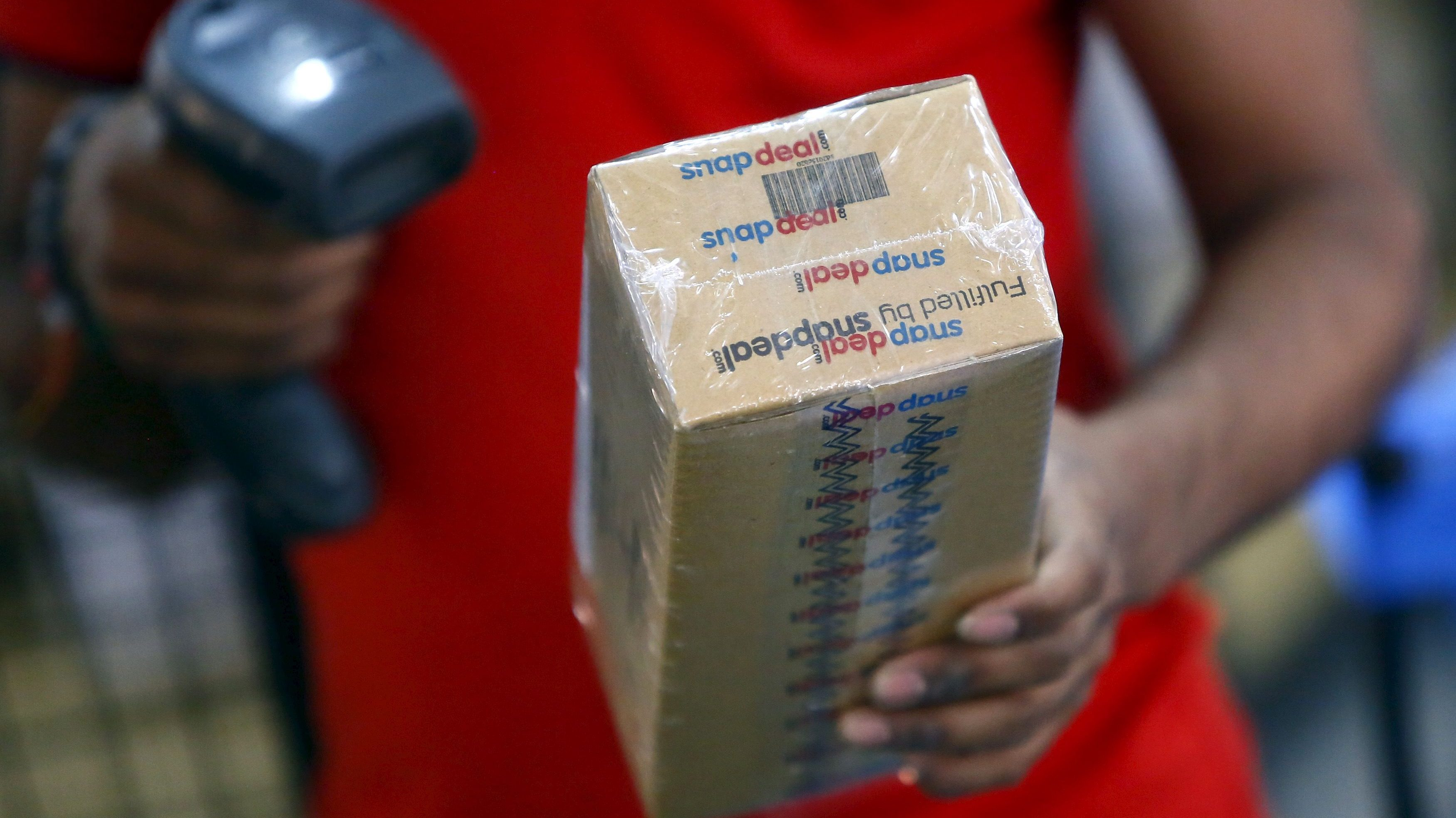 A worker of  Indian e-commerce company Snapdeal.com scans barcode on a box after it was packed at the company's warehouse in New Delhi April 20, 2015. After losing top engineering talent for years to America's tech heartland of Silicon Valley, India is luring them back as an e-commerce boom sparks a thriving start-up culture, unprecedented pay, and perks including free healthcare for in-laws. Picture taken April 20, 2015. To match INDIA-ECOMMERCE/WORKERS. REUTERS/Anindito Mukherjee - GF10000082309