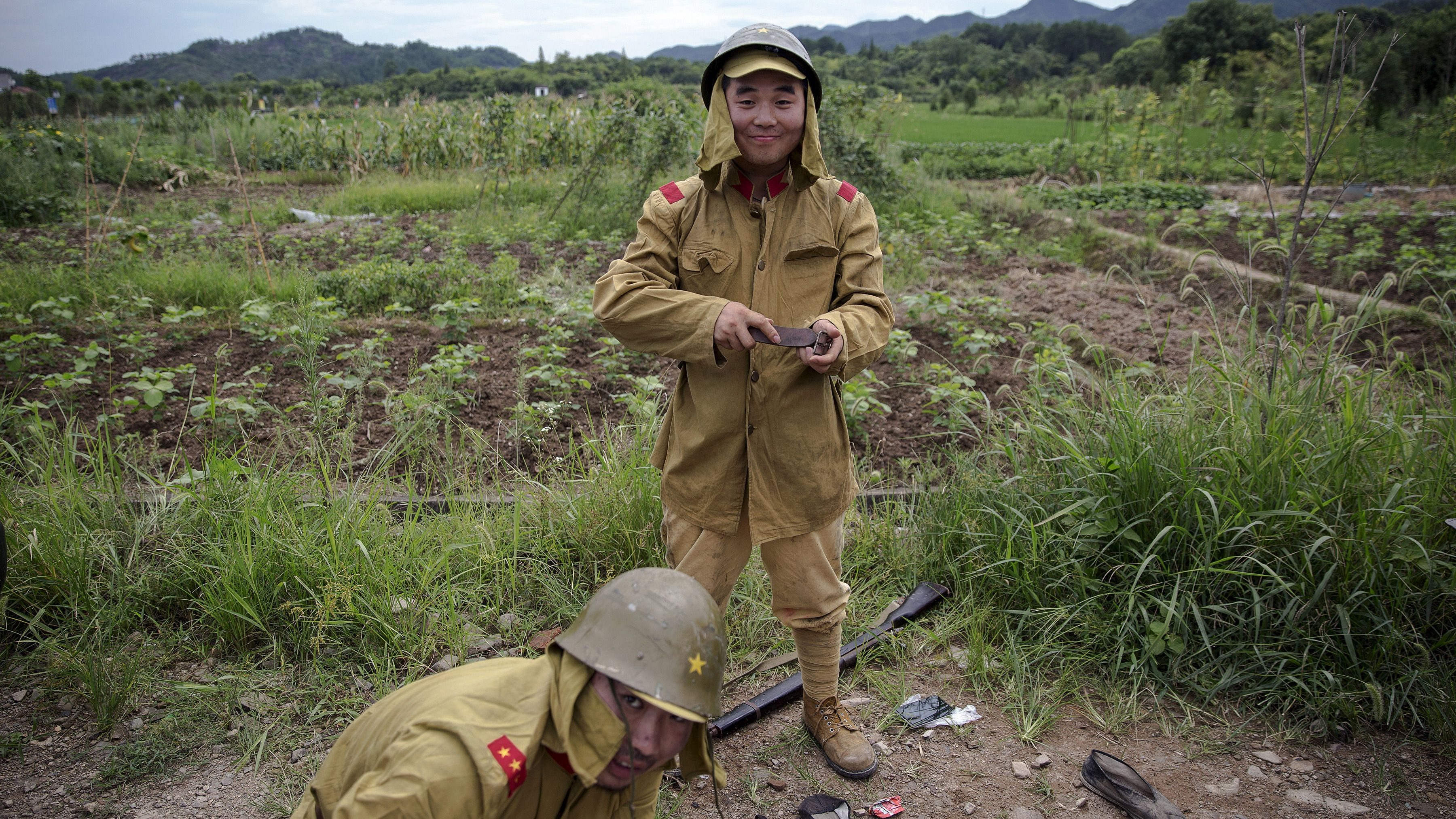 """Actors get dressed in historical Japanese army uniform costumes, minutes after playing small roles as Chinese soldiers on the set of """"The Last Prince"""" television series on location near Hengdian World Studios near Hengdian July 24, 2015. Extras and actors with smaller roles often take care of their own costumes and play more than one character in this production about the war against Japan. Director Li Xiaoqiang said the series is about a Qing Dynasty prince, who joined the Chinese nationalist army after suffering family misfortune. """"After he learnt more about the Communist Party, the prince began to understand what real revolution and the anti-Japanese war meant, and turned to the Communist Party to fight Japan"""", the director added. According to local media, more than 10 new movies, 12 TV dramas, 20 documentaries and 183 war-themed stage performances will be released in China to coincide with the 70th anniversary of the end of World War Two."""
