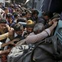 People board a passenger train at a railway station in New Delhi