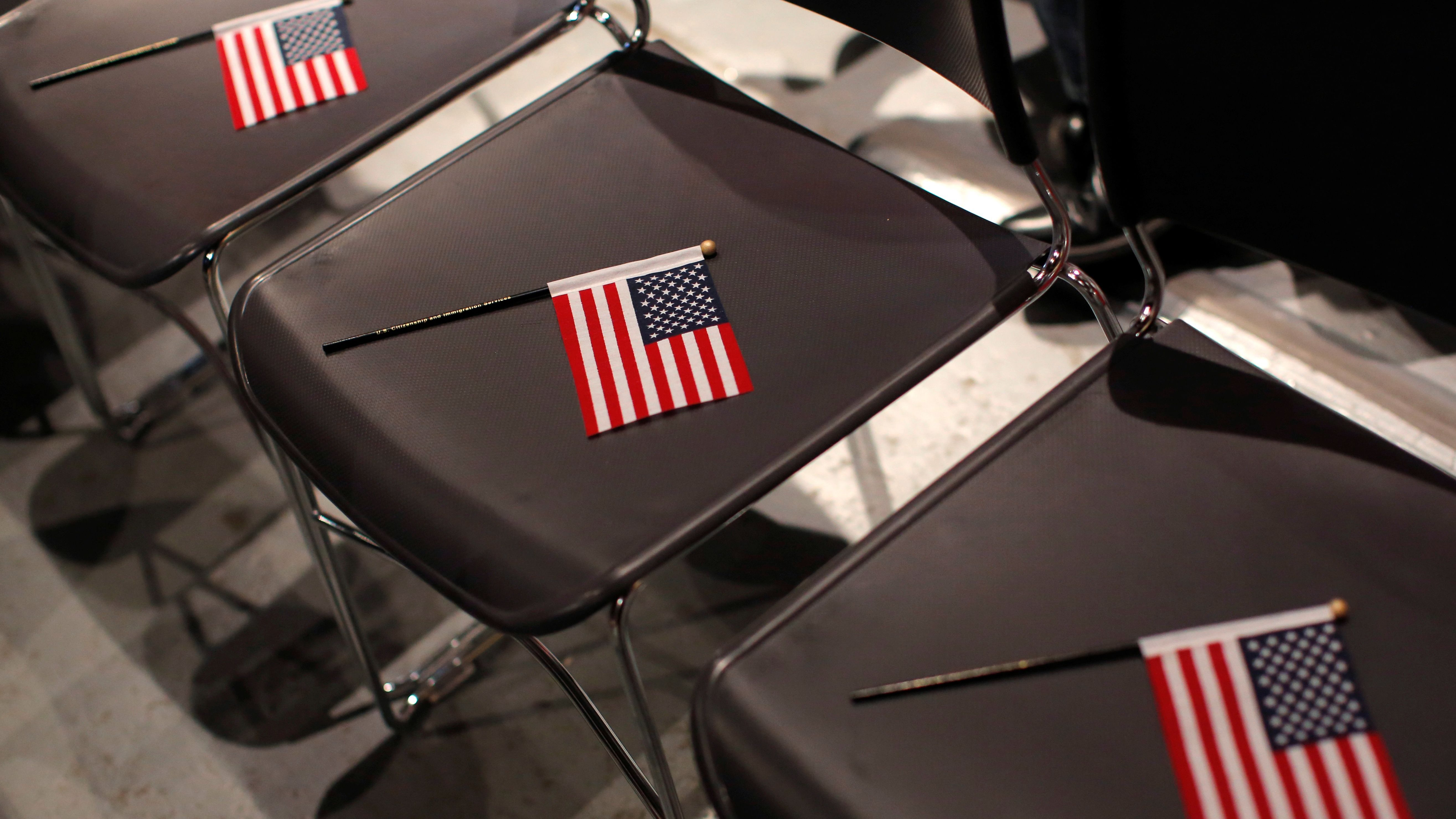 U.S. flags are placed on seats before a special citizenship ceremony for children at the Museum of Food and Drink in Brooklyn, New York City, U.S. December 23, 2016. REUTERS/Andrew Kelly - RC17FDA55C30