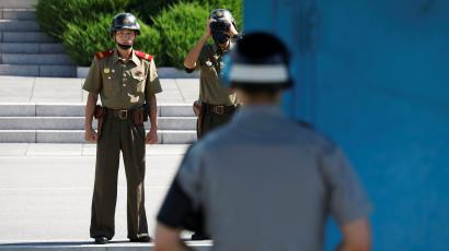 A North Korean soldier keeps watch toward the south through a binocular telescope as a South Korean soldier stands guard at the truce village of Panmunjom, South Korea, August 26, 2017.