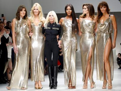 Italian designer Donatella Versace (3L) acknowledges the applause with former top models Carla Bruni (L), Claudia Schiffer, Naomi Campbell, Cindy Crawford and Helena Christensen (R) at the end of Versace Spring/Summer 2018 show at the Milan Fashion Week in Milan, Italy, September 22, 2017. REUTERS/Alessandro Garofalo - RC1F56EC1000