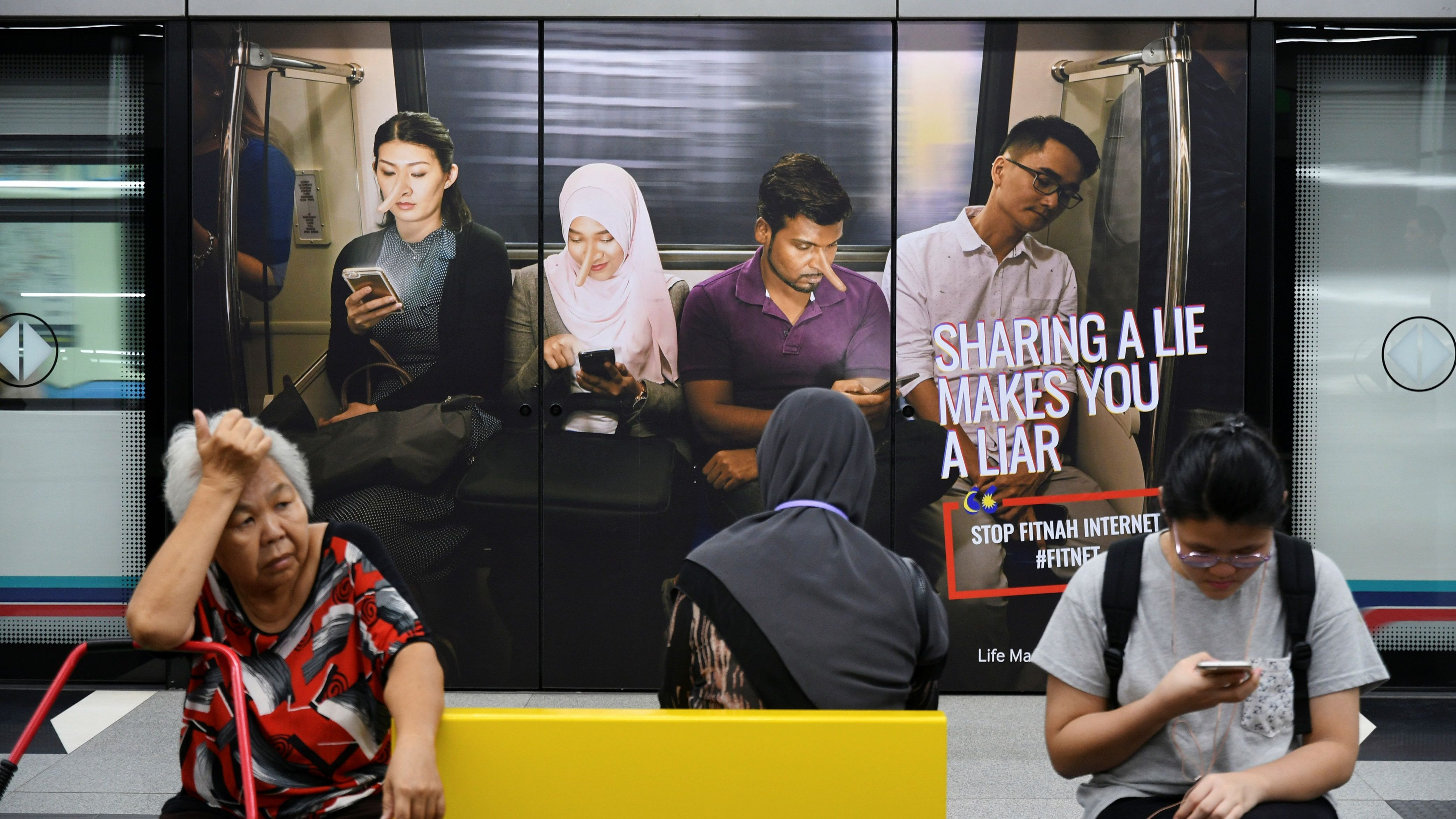 Commuters sit in front of an advertisement discouraging the dissemination of fake news, at a train station in Kuala Lumpur, Malaysia March 28, 2018. Picture taken March 28, 2018. REUTERS/Stringer - RC1DC110C000