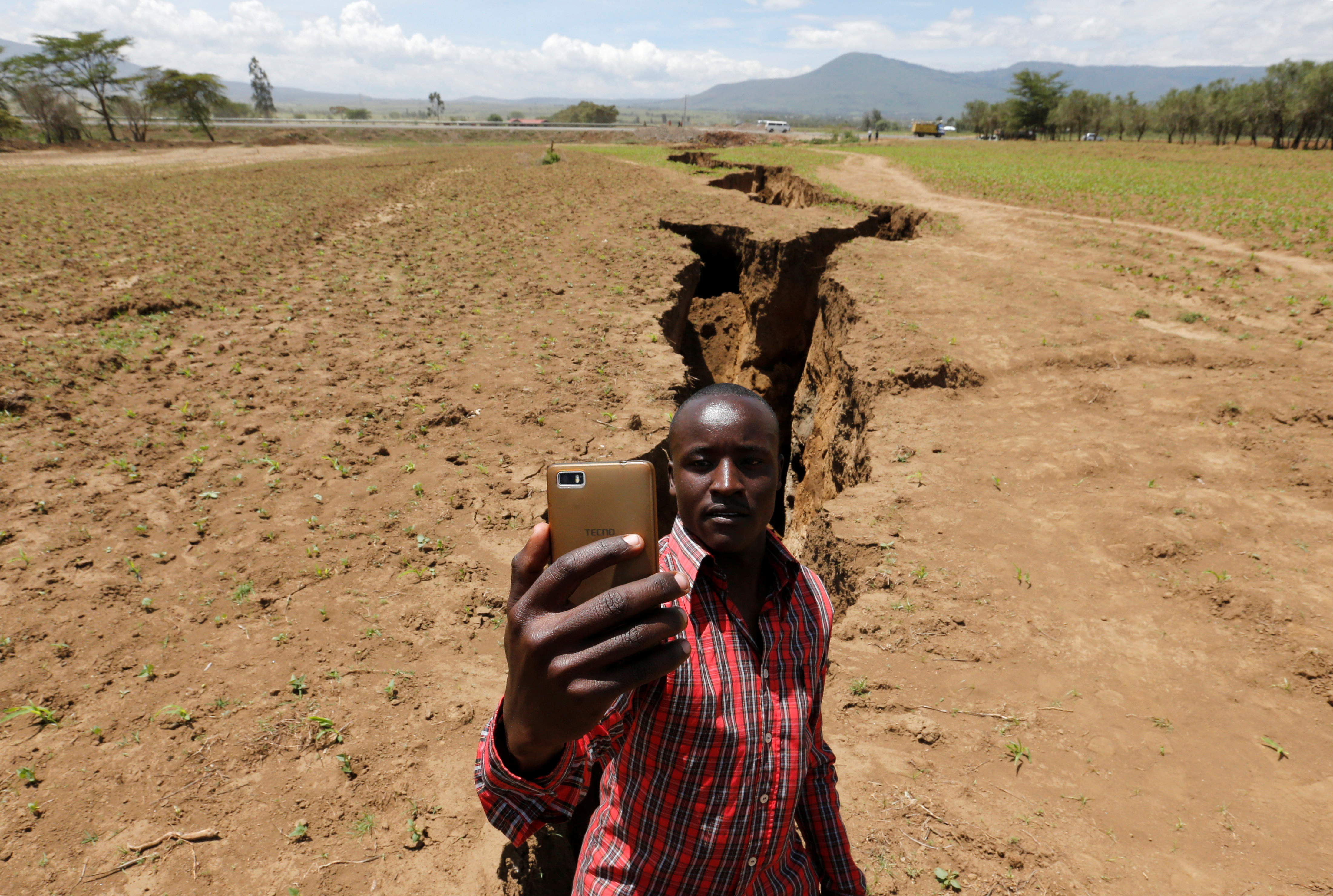 A man takes a selfie photograph near a chasm suspected to have been caused by a heavy downpour along an underground fault-line near the Rift Valley town of Mai Mahiu, Kenya March 28, 2018. Picture taken March 28, 2018.