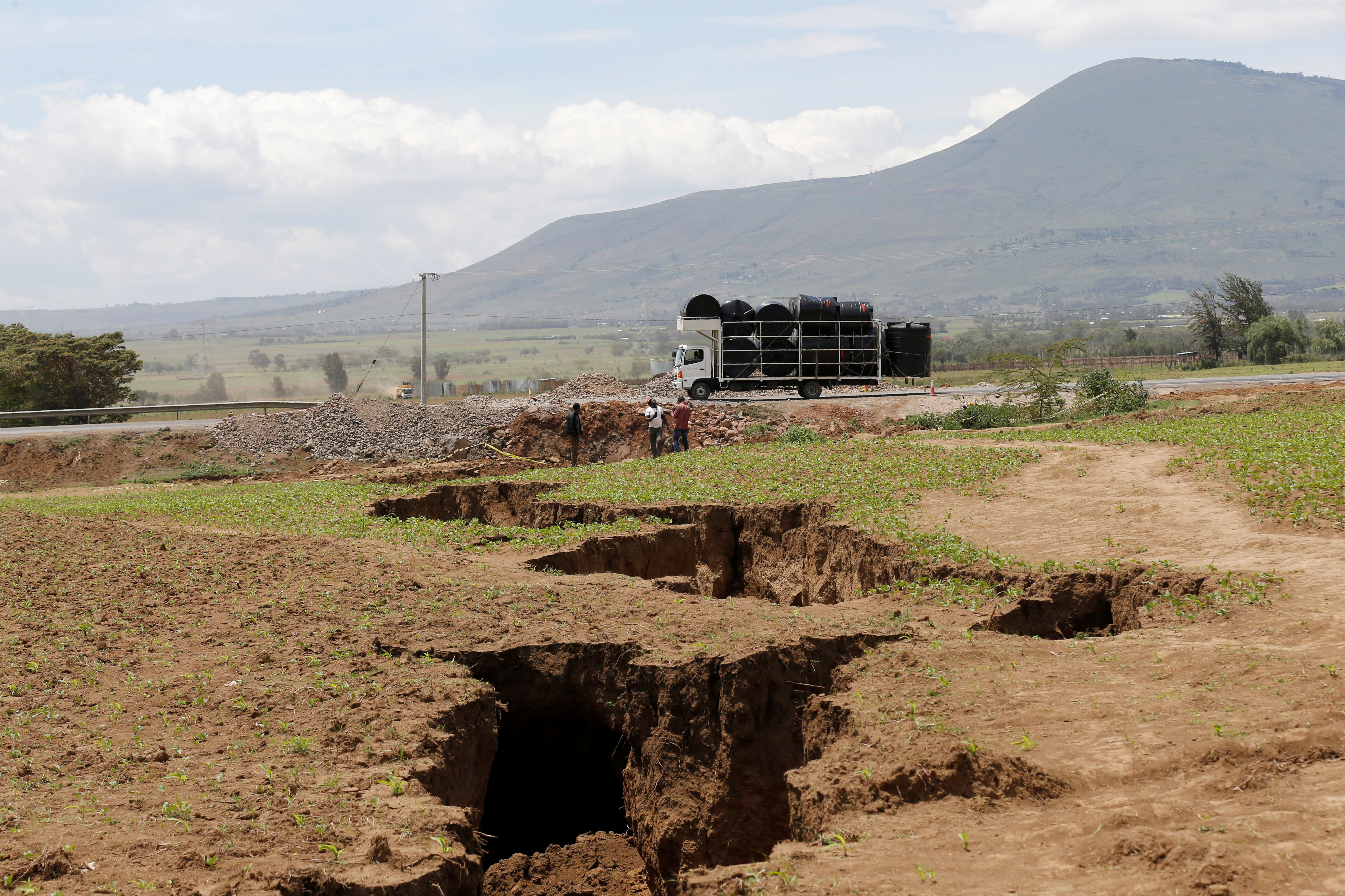 A truck drives near a chasm suspected to have been caused by a heavy downpour along an underground fault-line near the Rift Valley town of Mai Mahiu